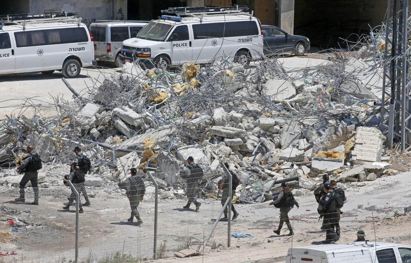 Des forces de sécurité israéliennes passaient lundi près de logements palestiniens démolis dans le village de Dar Salah, dans la bande de Gaza.