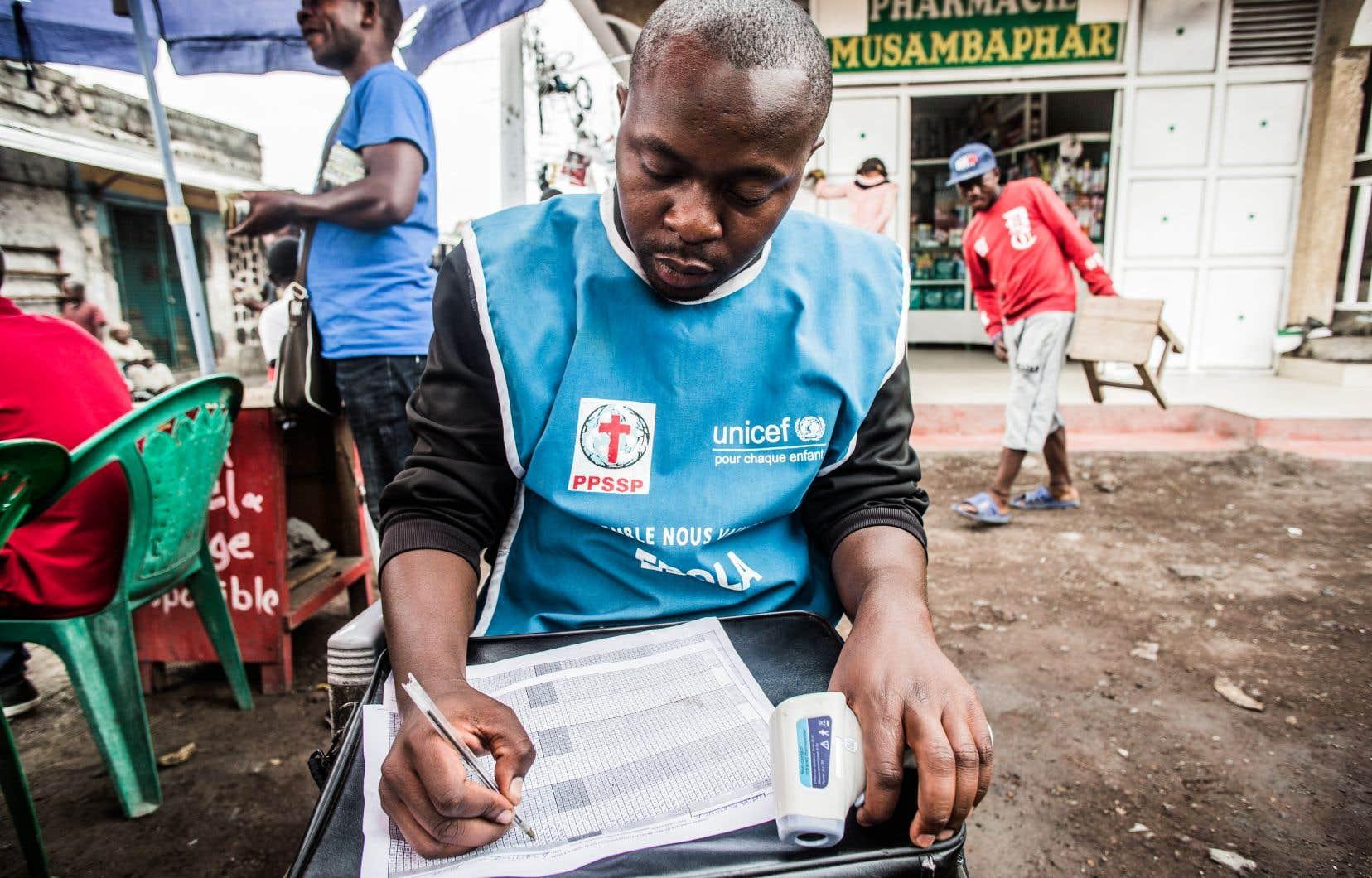 Un agent de santé enregistre les températures des personnes contrôlées à Goma le 31 juillet 2019.