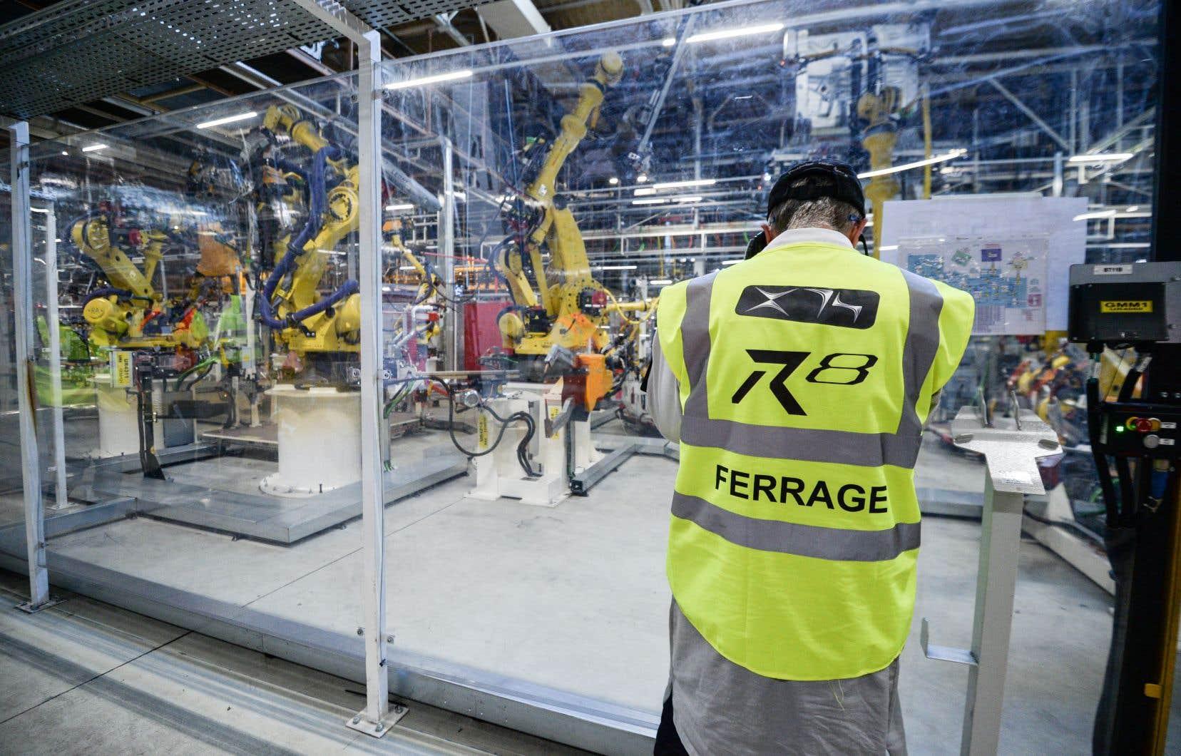 Selon un rapport de l'OCDE, 32% des emplois dans les pays membres de l'organisme pourraient être transformés avec l'automatisation des tâches et la multiplication des machines dans le monde du travail au cours des vingt prochaines années. Sur la photo, un employé dans une usine de production automobile en France surveille les tâches effectuées par des robots.
