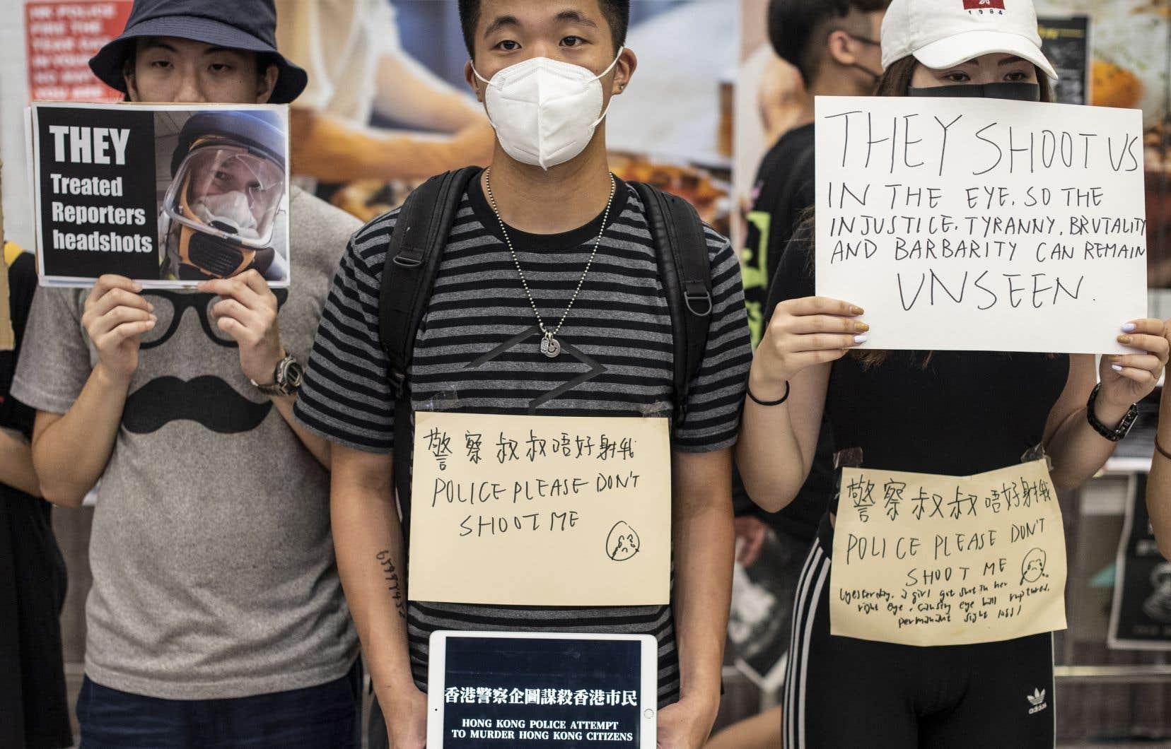 Des manifestants ont brandi des pancartes sur lesquelles ils accusent les policiers d'avoir recours à une violence disproportionnée.