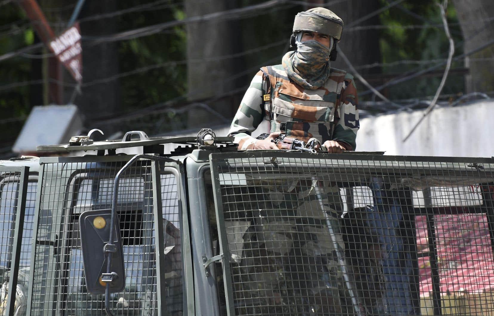 Un soldat de l'armée indienne reste en alerte dans un camion alors qu'il se trouvait dans un convoi à Srinagar, le 19 août.