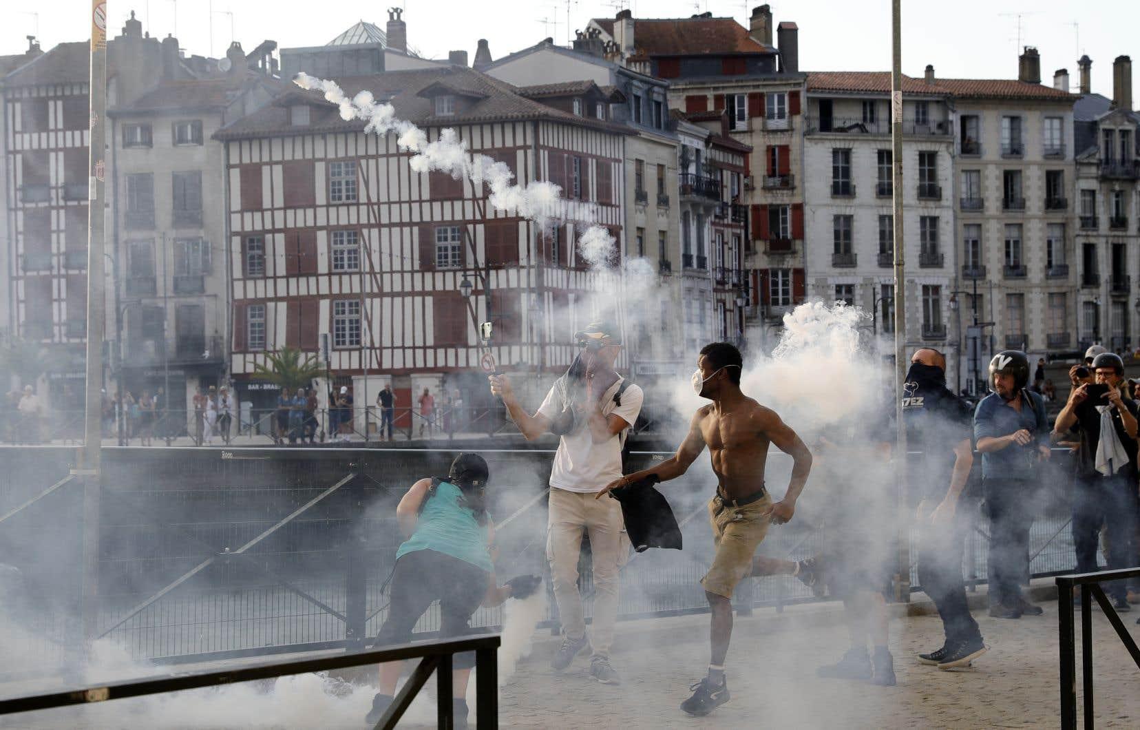Un manifestant à Bayonne lance un projectile vers des membres des forces de l'ordre, au milieu d'un nuage de gaz lacrymogènes.