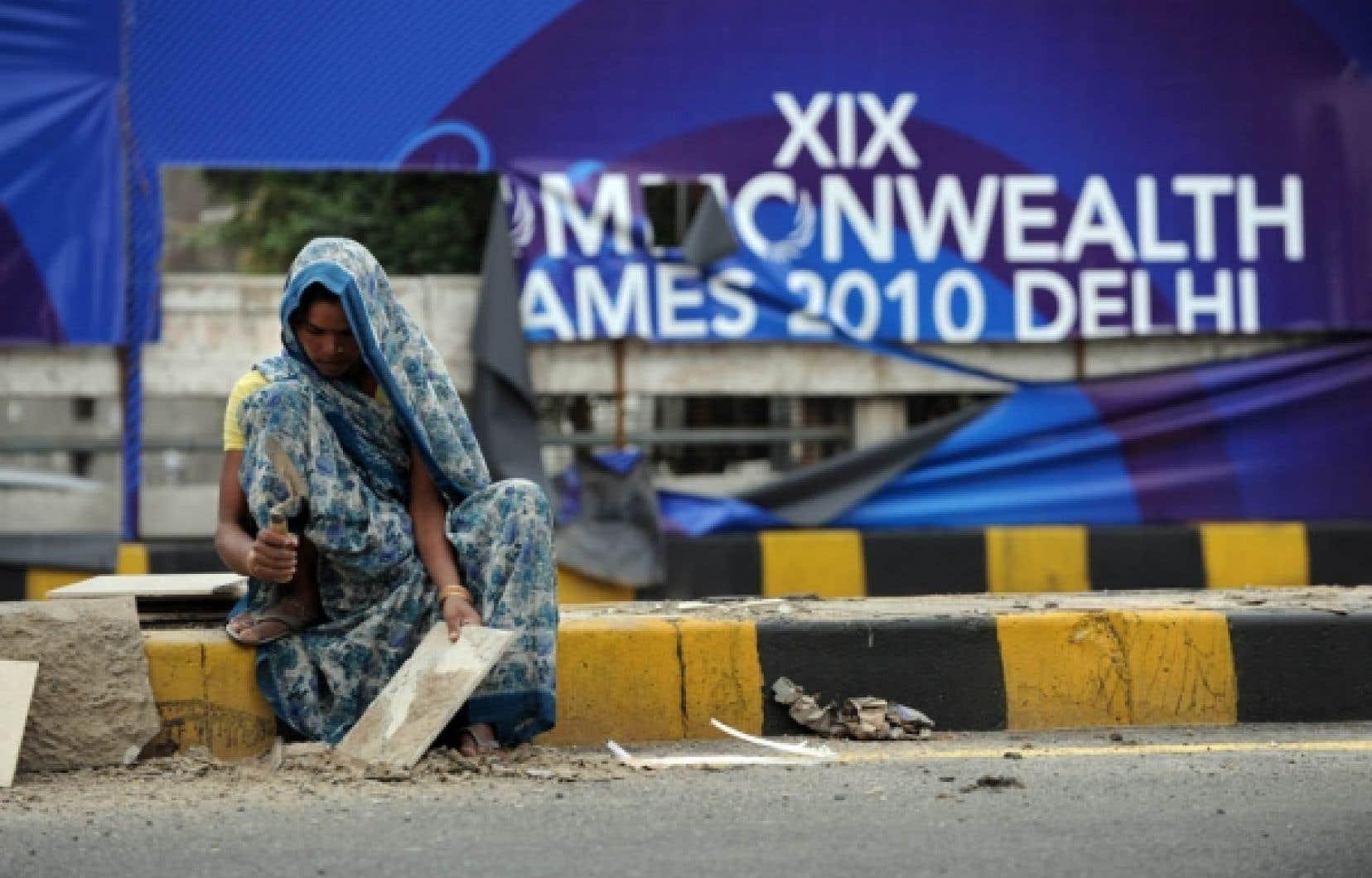 À New Delhi, une femme est photographiée devant une affiche des Jeux du Commonwealth.<br />