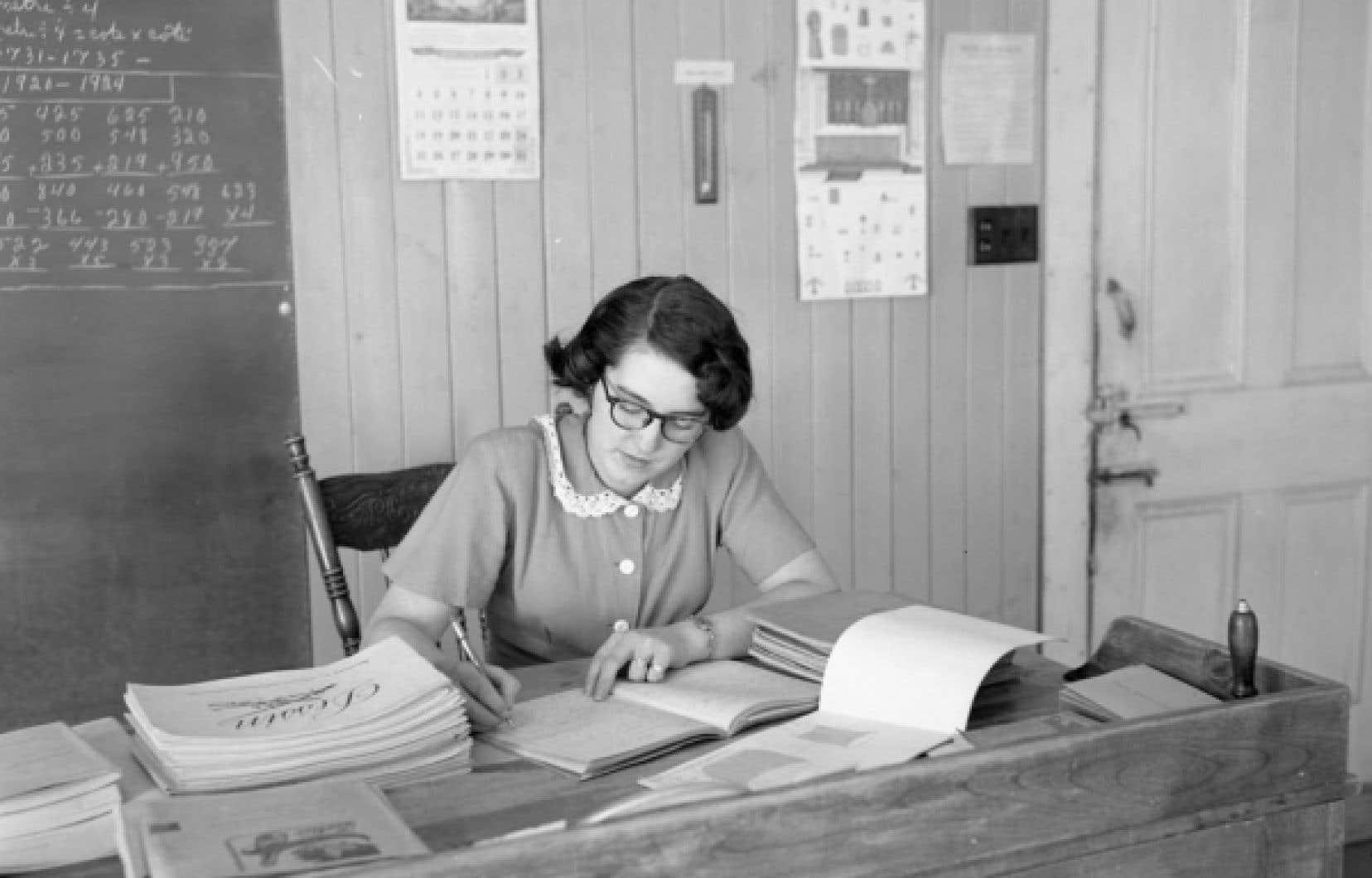 Institutrice corrigeant les travaux des enfants dans une &eacute;cole de rang de Saint-Henri-de-L&eacute;vis, en 1952.<br />