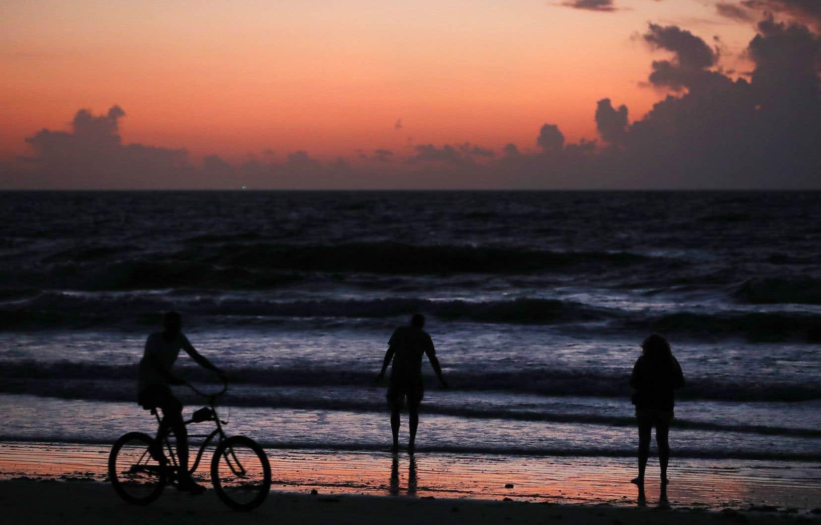 Des gens regardent le lever de soleil à Coco Beach, en Floride, où l'ouragan «Dorian» se rapproche progressivement.