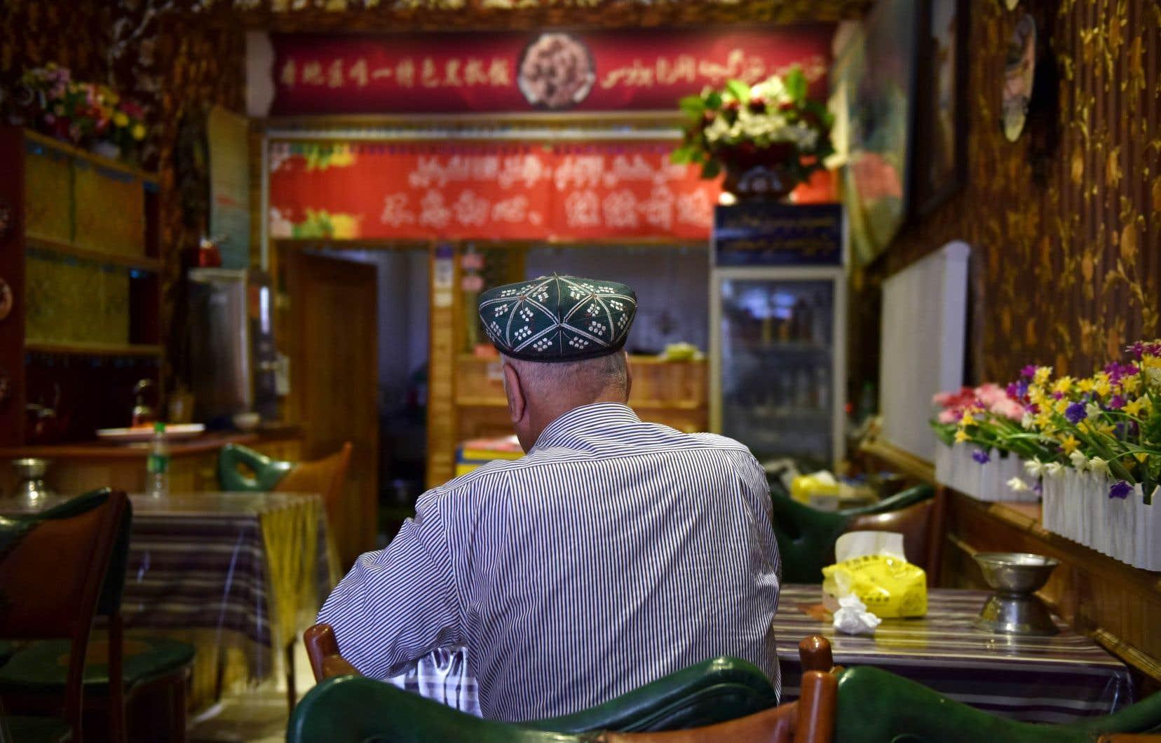 Un homme âgé d'ethnie ouïgoure s'assoit dans un restaurant de Hotan, dans le Xinjiang.