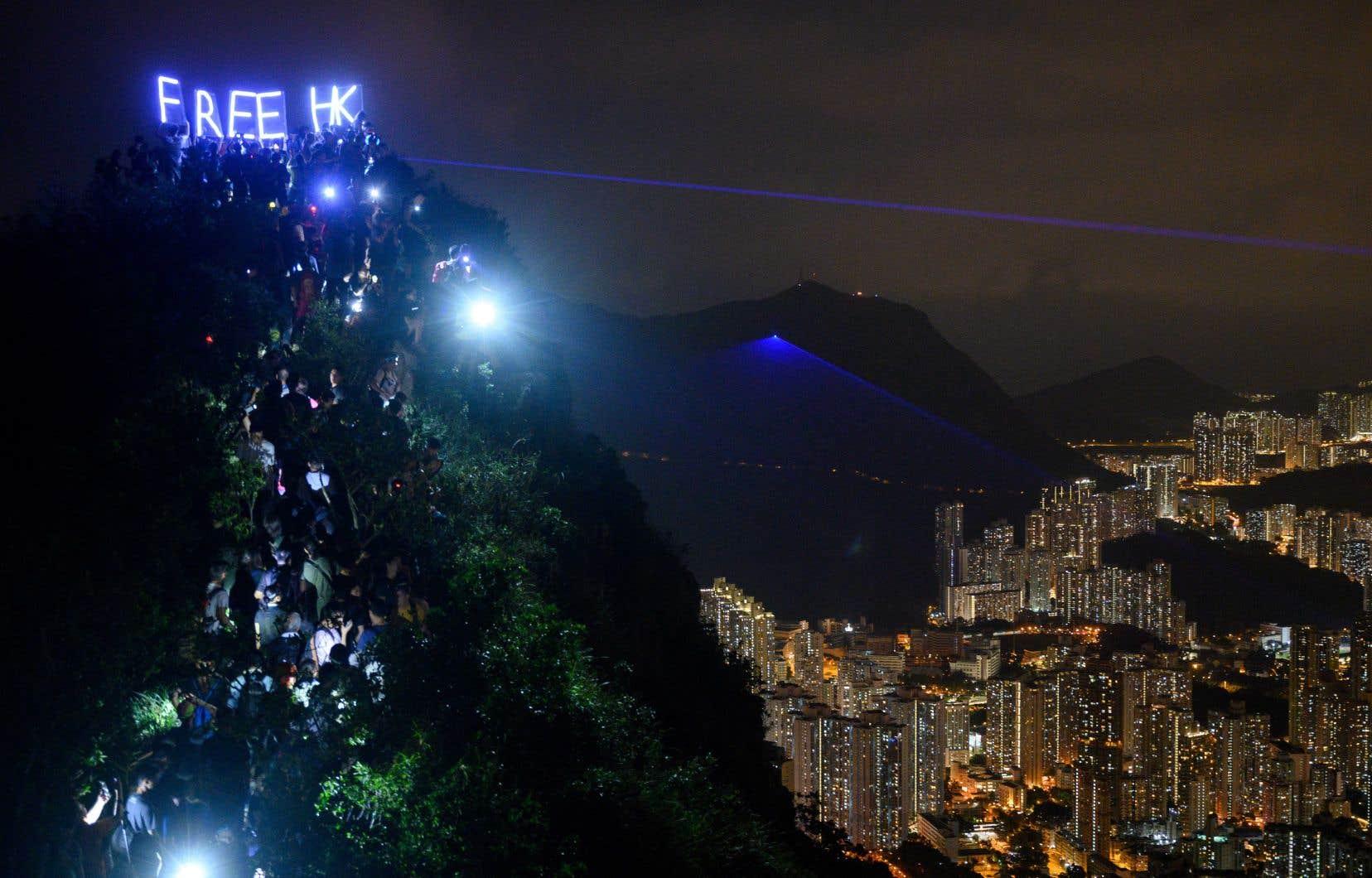 Des milliers de manifestants prodémocratie ont illuminé vendredi soir de torches, lanternes ou pointeurs laser deux des collines de Hong Kong, profitant de l'ouverture de festivités traditionnelles pour rappeler leur détermination.