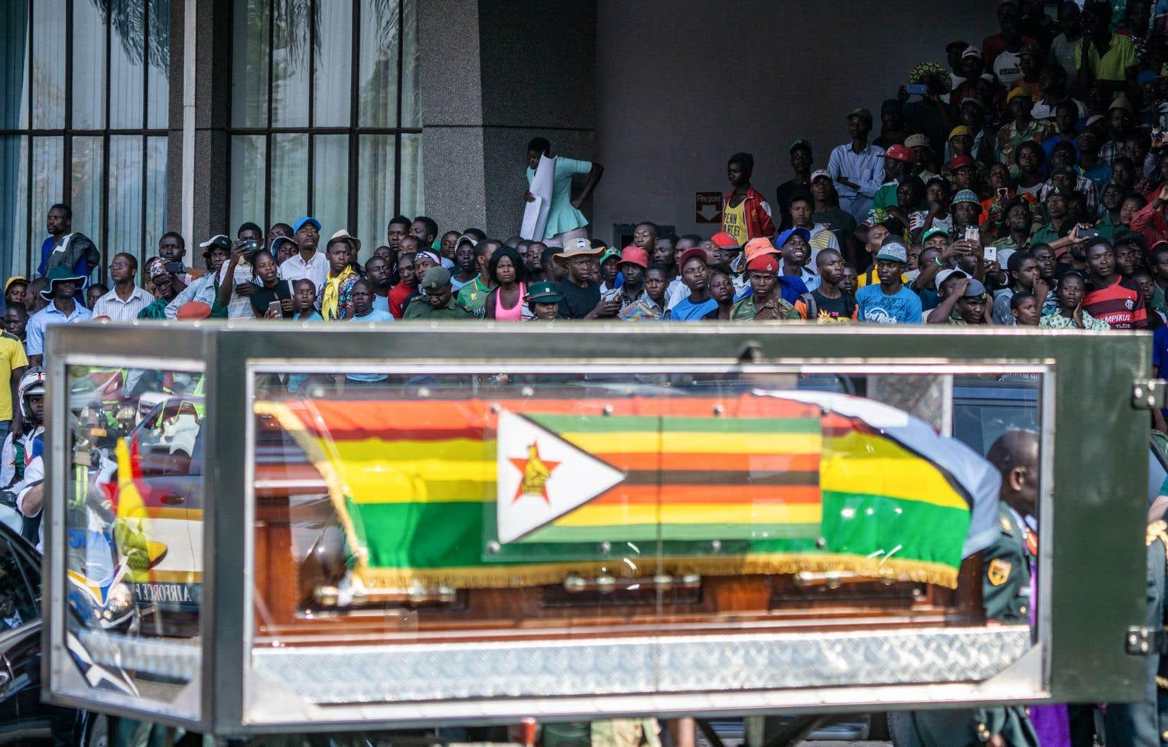La foule regarde le cercueil du défunt président zimbabwéen, Robert Mugabe, chargé dans une voiture, lors d'une cérémonie d'adieu organisée à Harare.