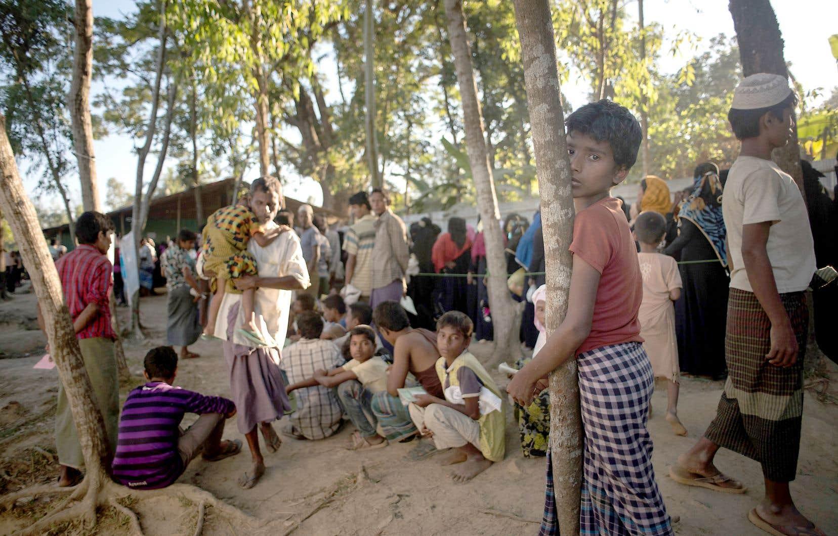 Des réfugiés rohingyas font la file dans un camp au Bangladesh pour recevoir de l'aide alimentaire. Quelque 740000 musulmans rohingyas ont fui l'État myanmarais de Rakhine en août 2017, après une opération de répression de l'armée du Myanmar, pays à forte majorité bouddhiste.