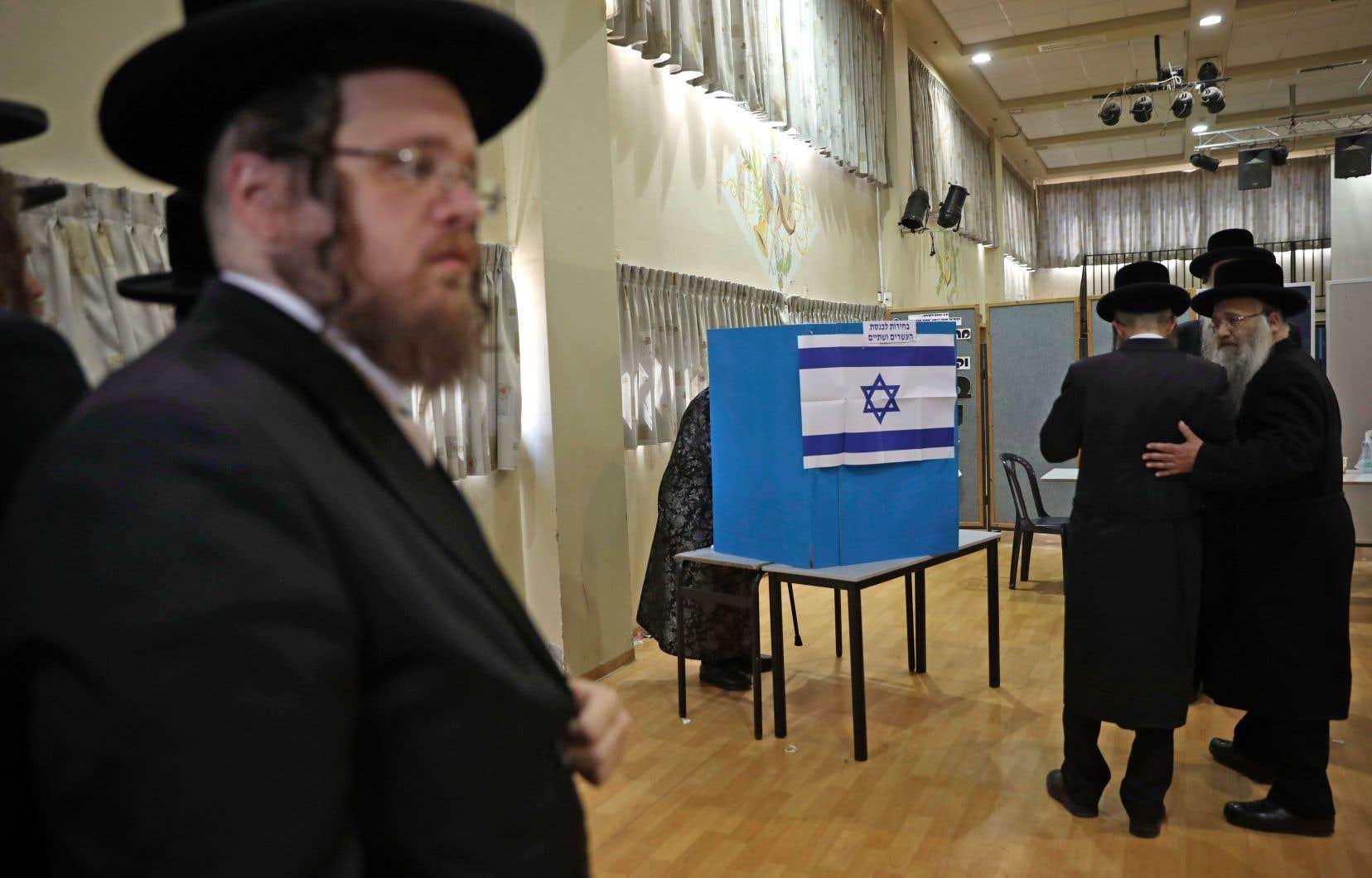 À Bnei Brak, des juifs ultra-orthodoxes attendent que leur rabbin enregistre son vote pour se rendre aux urnes à leur tour.