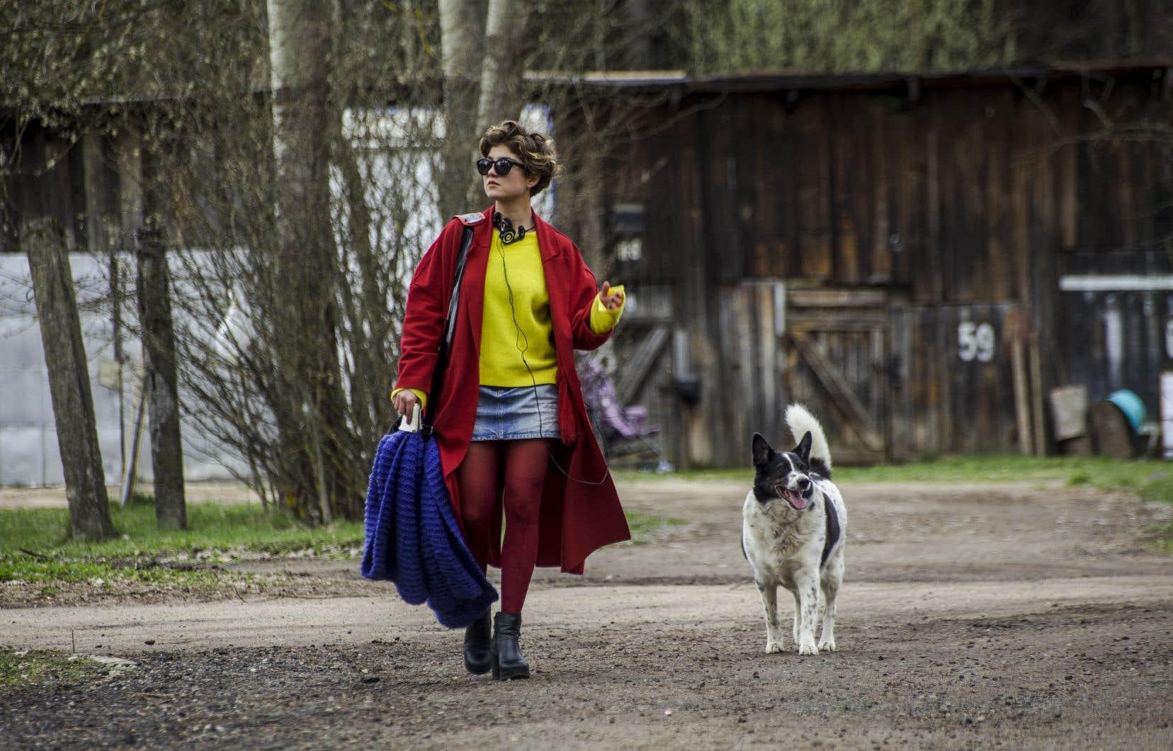 Manteau rouge, grand foulard mauve, minijupe, lunettes fumées ostentatoires et les écouteurs sur les oreilles, aucun artifice n'est de trop pour permettre à Velya  de marquer  sa présence,  sa différence.