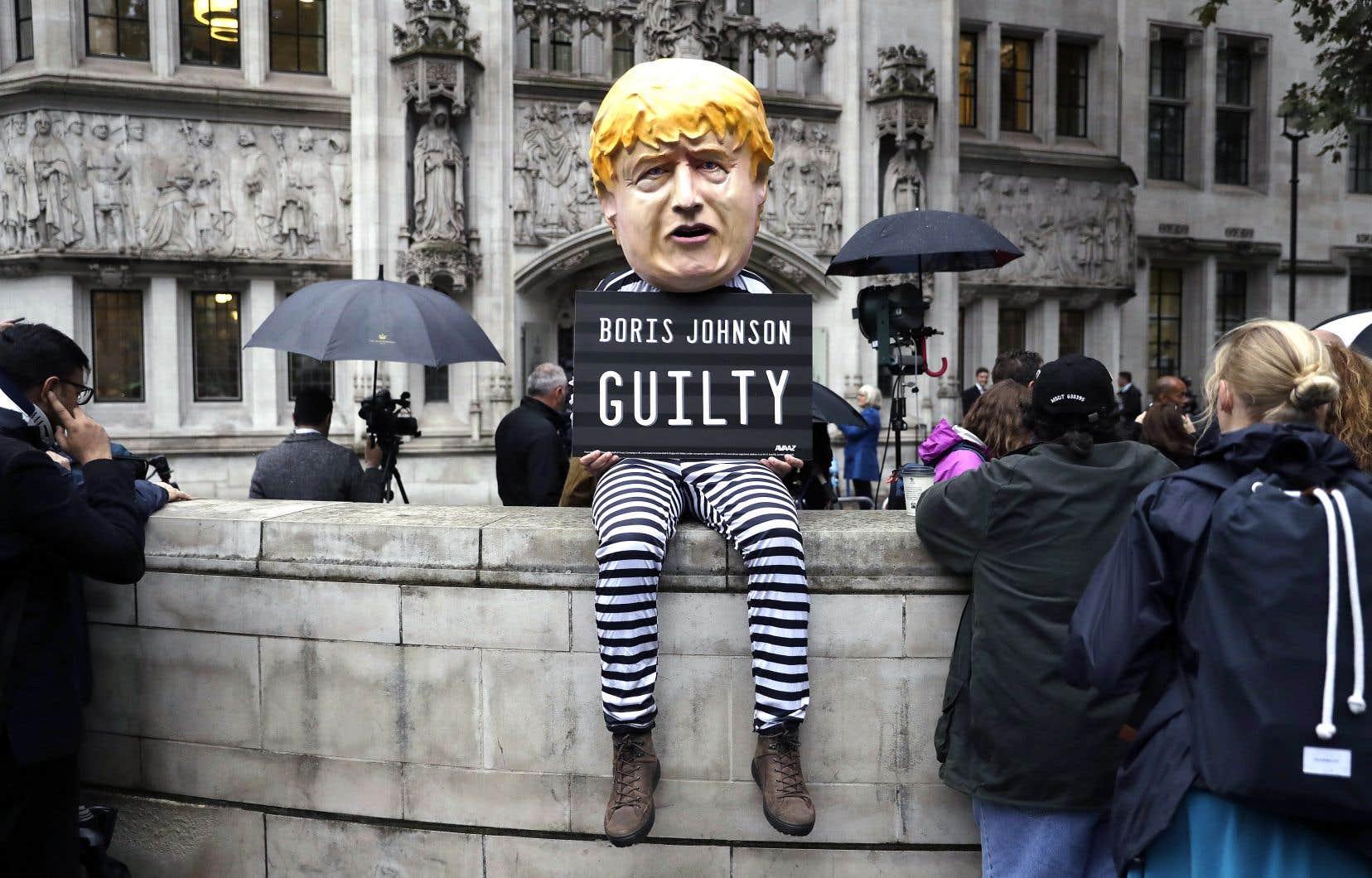 Un manifestant portant un costume caricatural du premier ministre Boris Johnson se tenait devant la Cour suprême du Royaume-Uni, mardi, lorsque ses magistrats ont prononcé leur décision unanime sur l'illégalité de la prorogation des travaux parlementaires.
