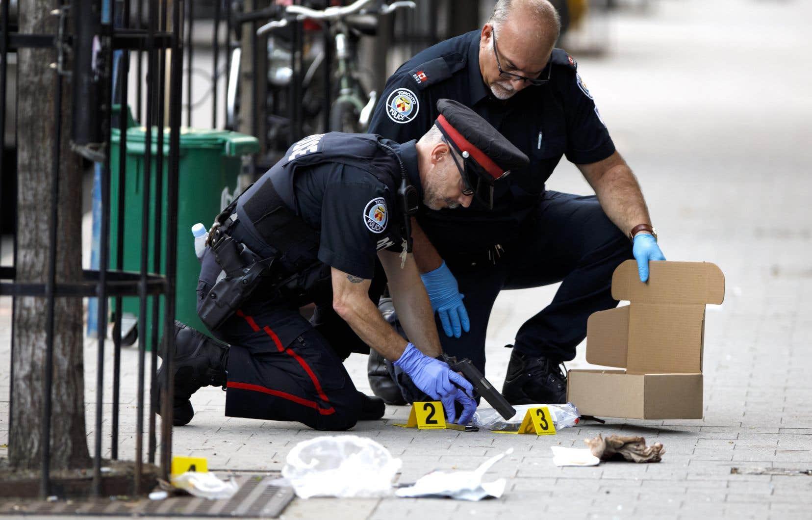 Des policiers examinaient une arme de poing après une fusillade à Toronto, en août dernier.