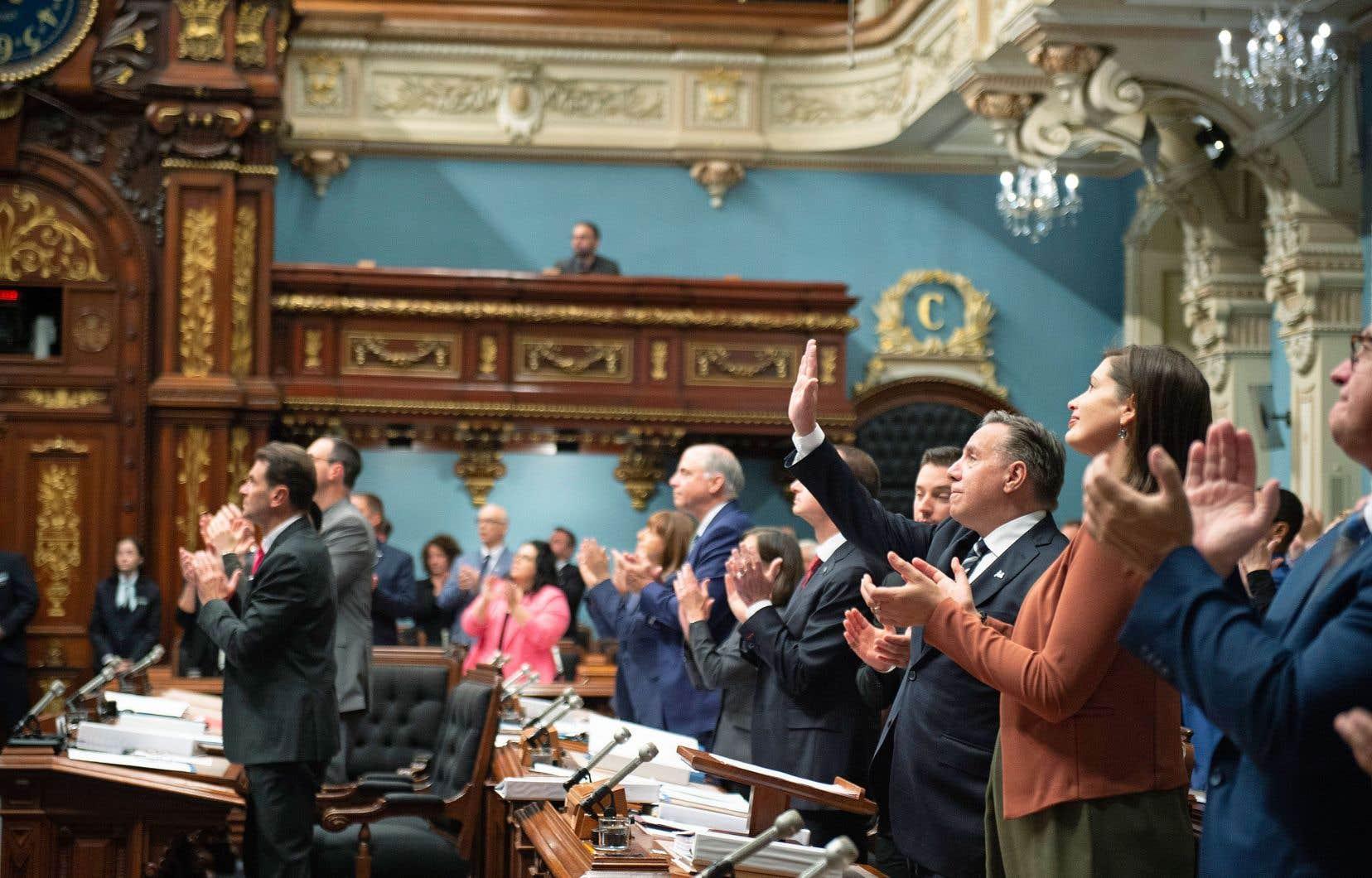 Le premier ministre François Legault salue les représentants des Premières Nations et des Inuits pendant que les autres parlementaires applaudissent à la suite du discours par lequel le Québec a présenté ses excuses aux Autochtones victimes de discrimination systémique.