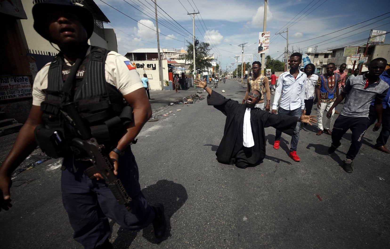 Un activiste a supplié à genoux un policier de laisser des manifestants ériger une barricade sur une route principale de Port-au-Prince, mercredi, en guise de protestation contre le gouvernement Moïse.