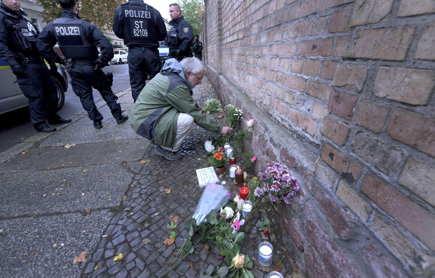Un homme déposait une gerbe de fleurs devant la synagogue de Halle jeudi, au lendemain d'une attaque d'un antisémite qui a fait deux morts.