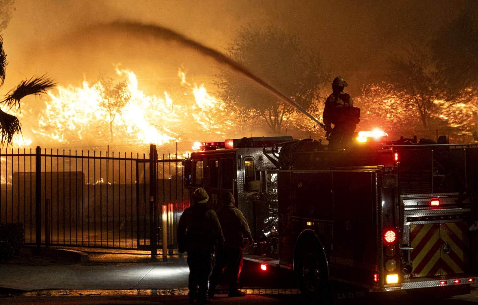 Des pompiers tentaient d'arrêter les flammes attisées par le vent dans le quartier de Sylmar, vendredi, à Los Angeles.