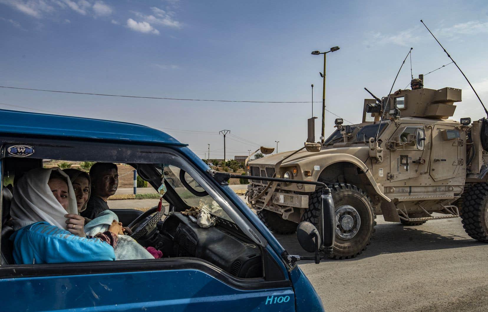 Une famille fuyait Ras al-Aïn dimanche alors qu'un convoit de véhicules américains traversait Tal Tamr, transportant du matériel militaire.