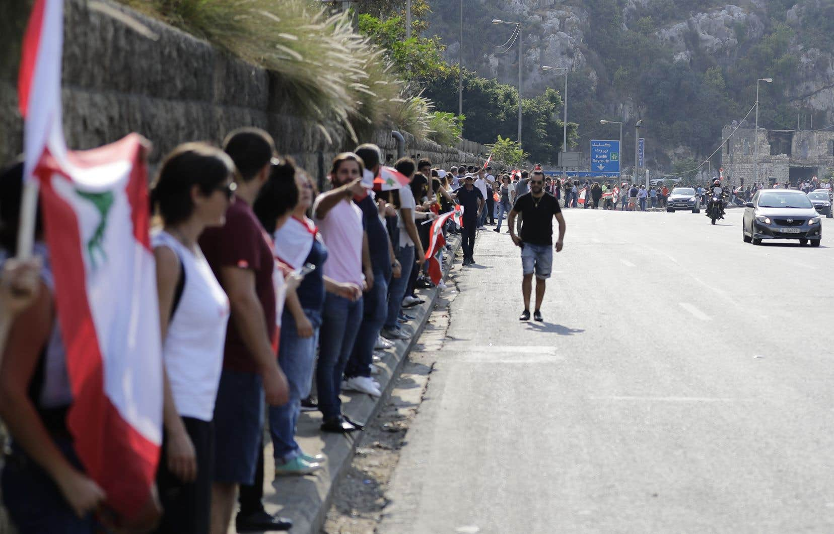 Rejoignant à pied, en voiture, à vélo ou à moto l'autoroute qui longe le pays en bord de Méditerranée, hommes, femmes et enfants se sont retrouvés pour se tenir la main en agitant des drapeaux libanais.