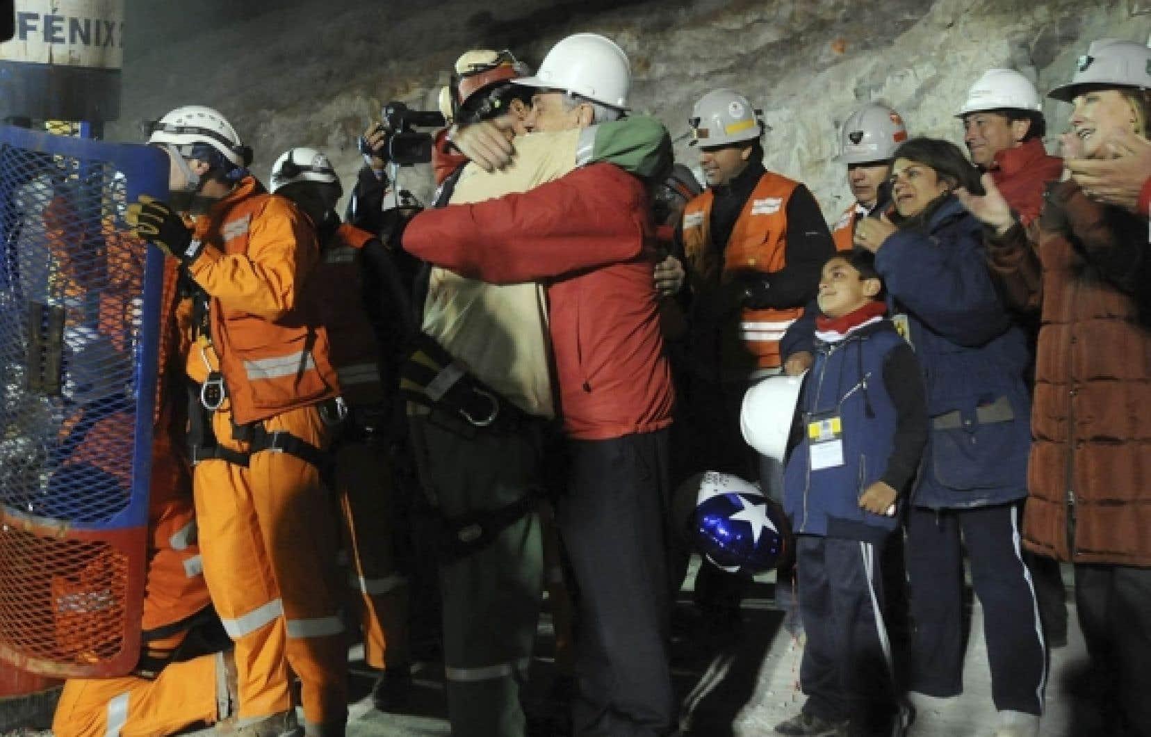 Florencio Avalos, le premier des 33 mineurs &agrave; sortir sain et sauf de la mine de San Jos&eacute;, re&ccedil;oit l&rsquo;accolade du pr&eacute;sident chilien, Sebasti&aacute;n Pi&ntilde;era.<br />