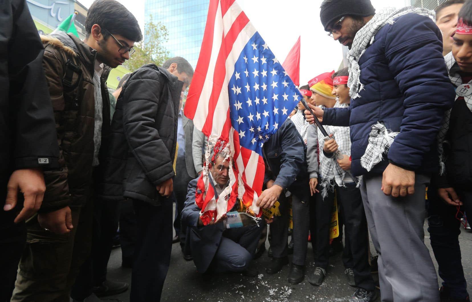 Des manifestants iraniens ont mis le feu à un drapeau américain, lundi, devant l'ancienne ambassade des États-Unis à Téhéran, pour marquer le 40eanniversaire de la prise en otage des diplomates américains en novembre 1979.