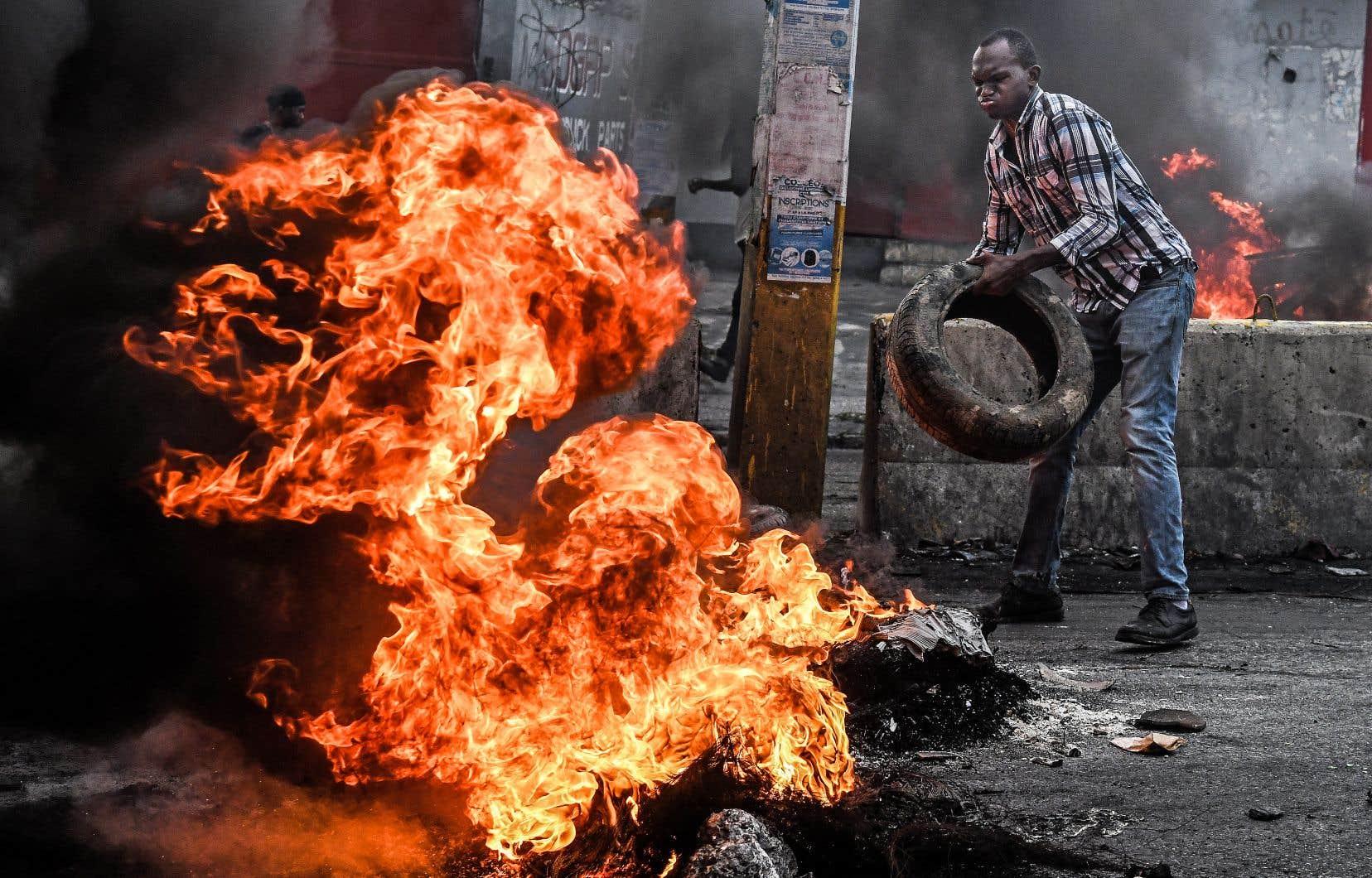 Les contestataires haïtiens font brûler des pneus pour ériger des barricades dans les rues de Port-au-Prince.