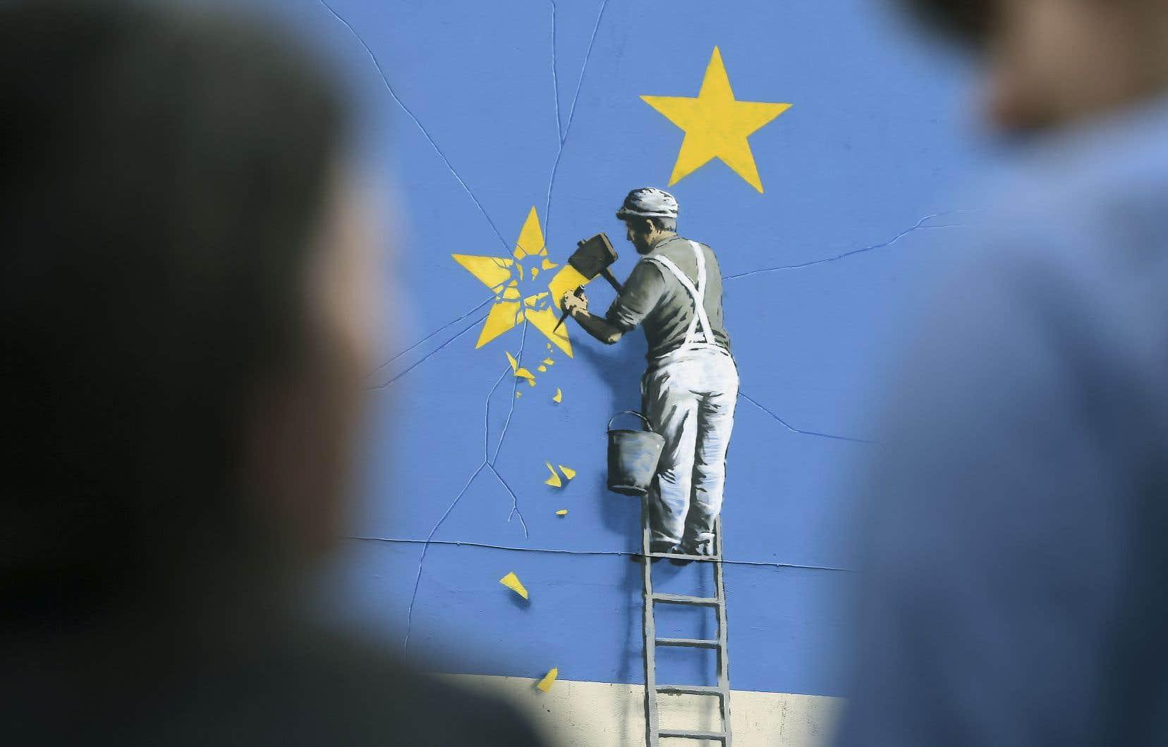 À Douvres, au Royaume-Uni, une murale de l'artiste Banksy montre un travailleur qui taille une étoile de l'Union européenne.