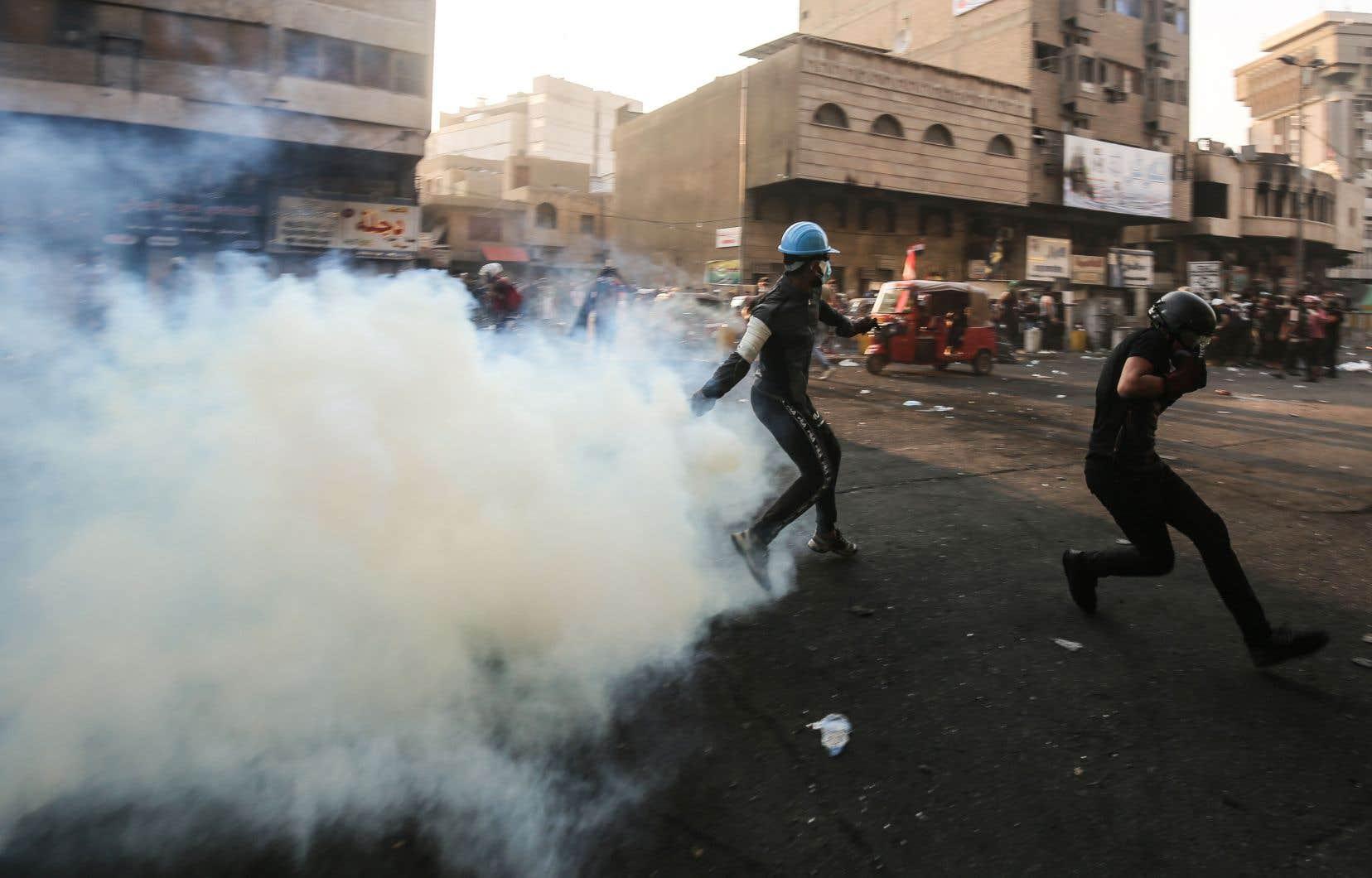 L'Irak fait face à son premier mouvement social spontané. Sur la photo, un manifestant renvoie une bombe lacrymogène lancée par les forces de l'ordre, à Bagdad.