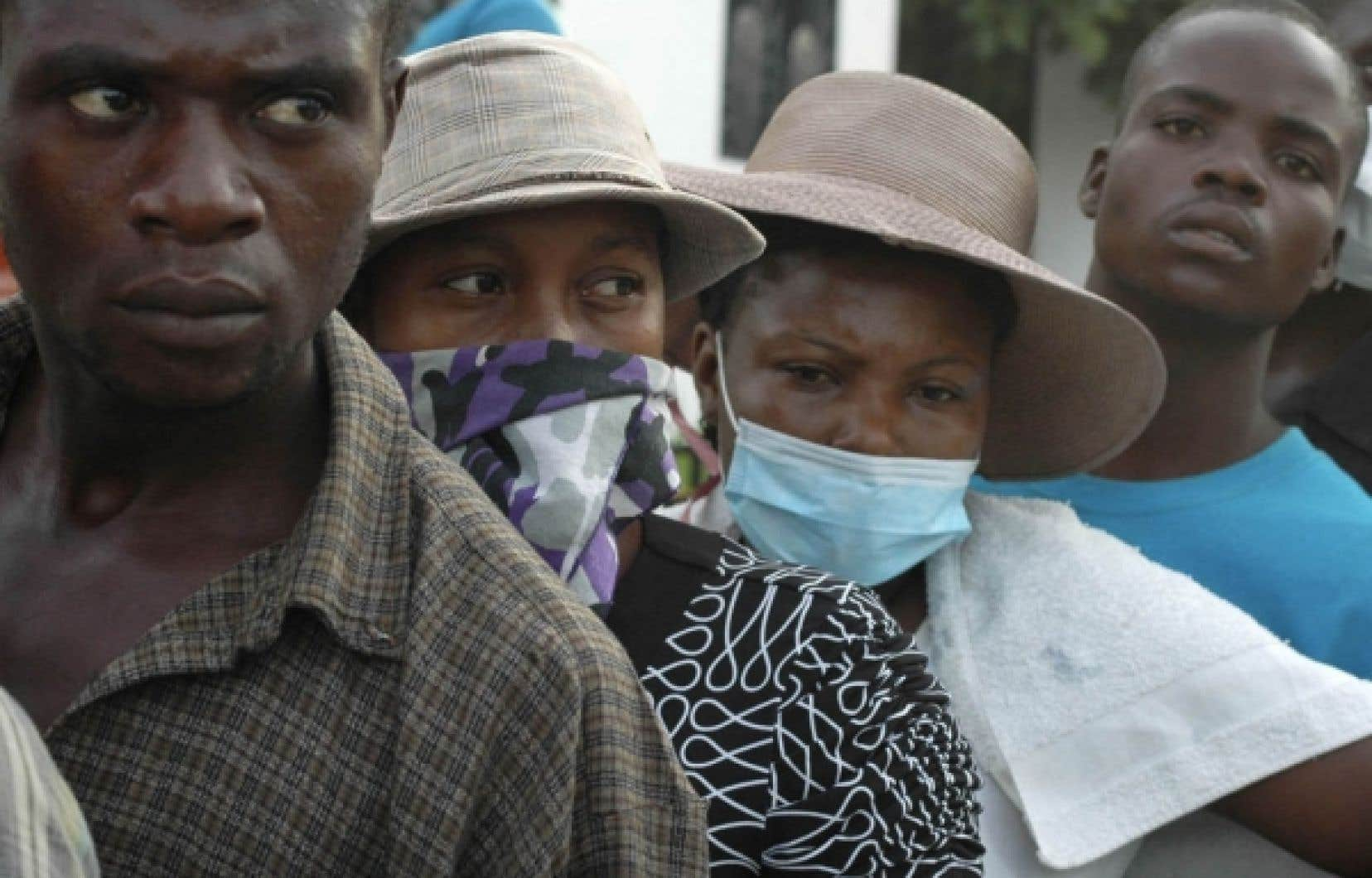 Des parents d'Haïtiens souffrant du choléra attendent des nouvelles de leurs proches à l'extérieur d'un hôpital de la ville de Saint-Marc. <br />