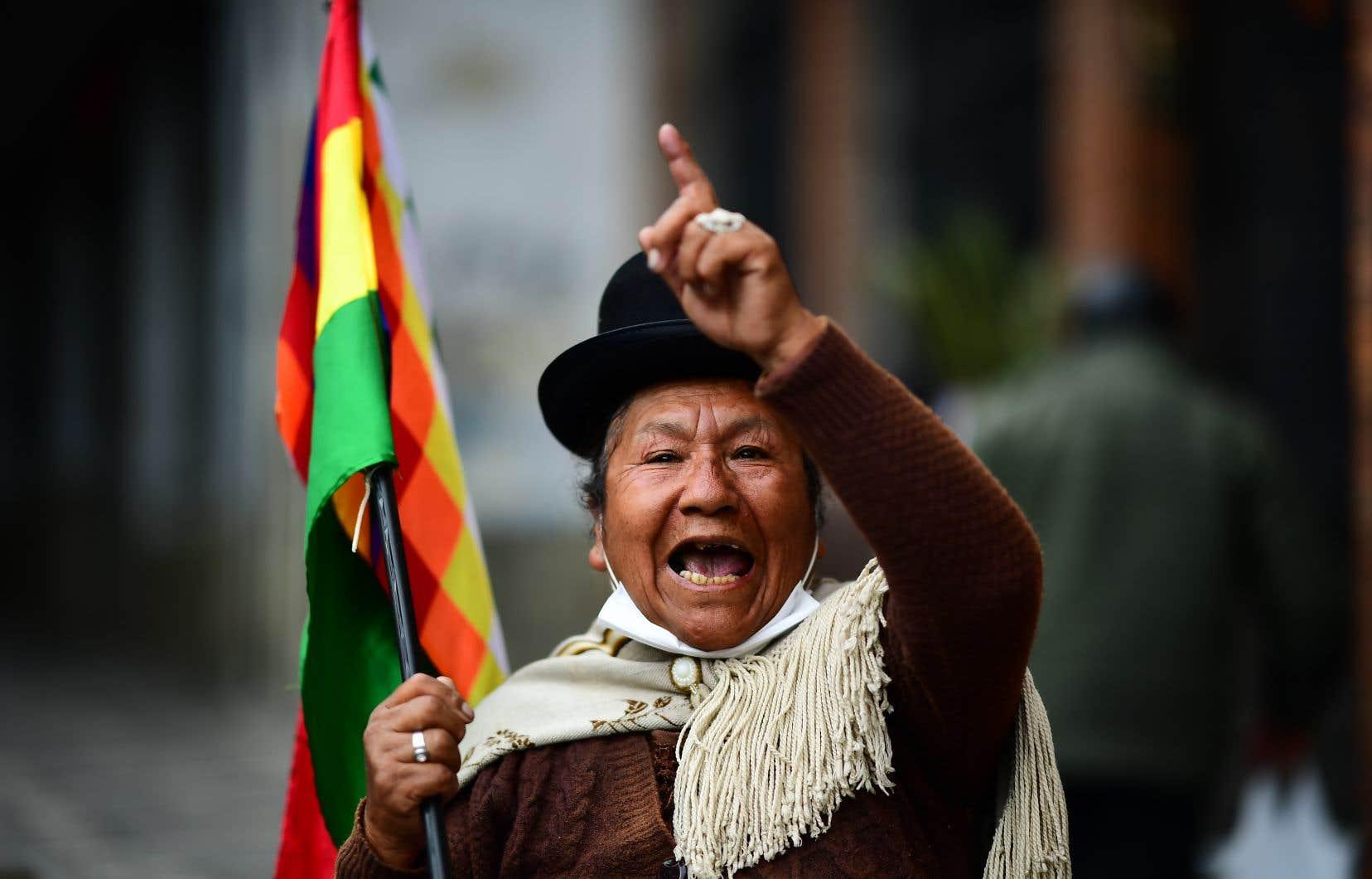 Une manifestante brandit un Wiphala, le drapeau andin indigène multicolore que l'ex-président Evo Morales a introduit comme symbole national en 2009.