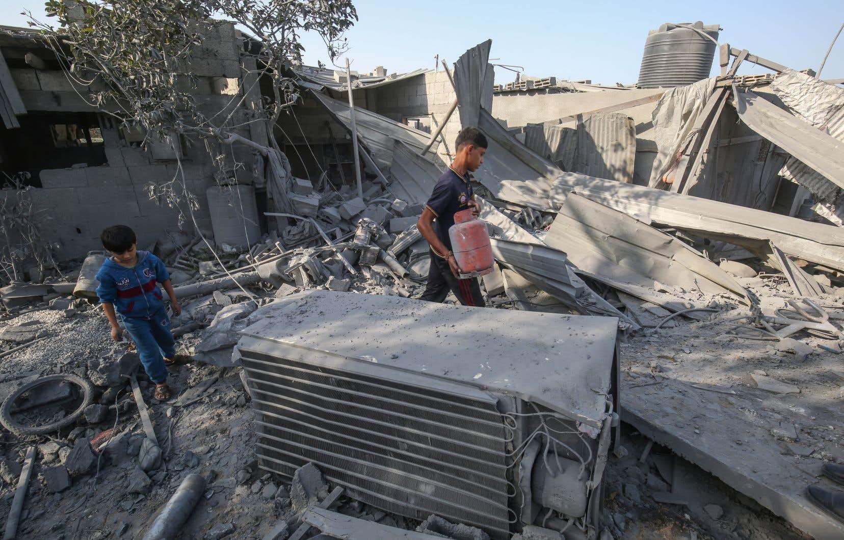 Deux jeunes Palestiniens constatent l'étendue des dommages causés par les frappes israéliennes à Khan Younès, dans le sud de la bande de Gaza.
