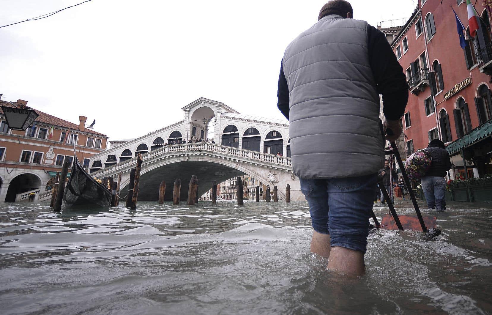 Un homme pousse un chariot dans une rue inondée de Venise, à proximité du Pont du Rialto.