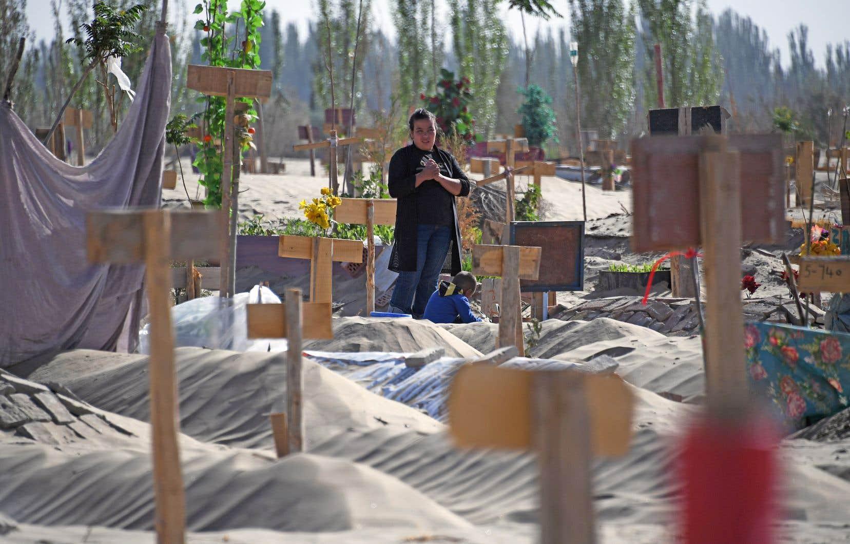 Une femme se recueillait en mai dernier dans un cimetière ouïghour de la région du Xinjiang.