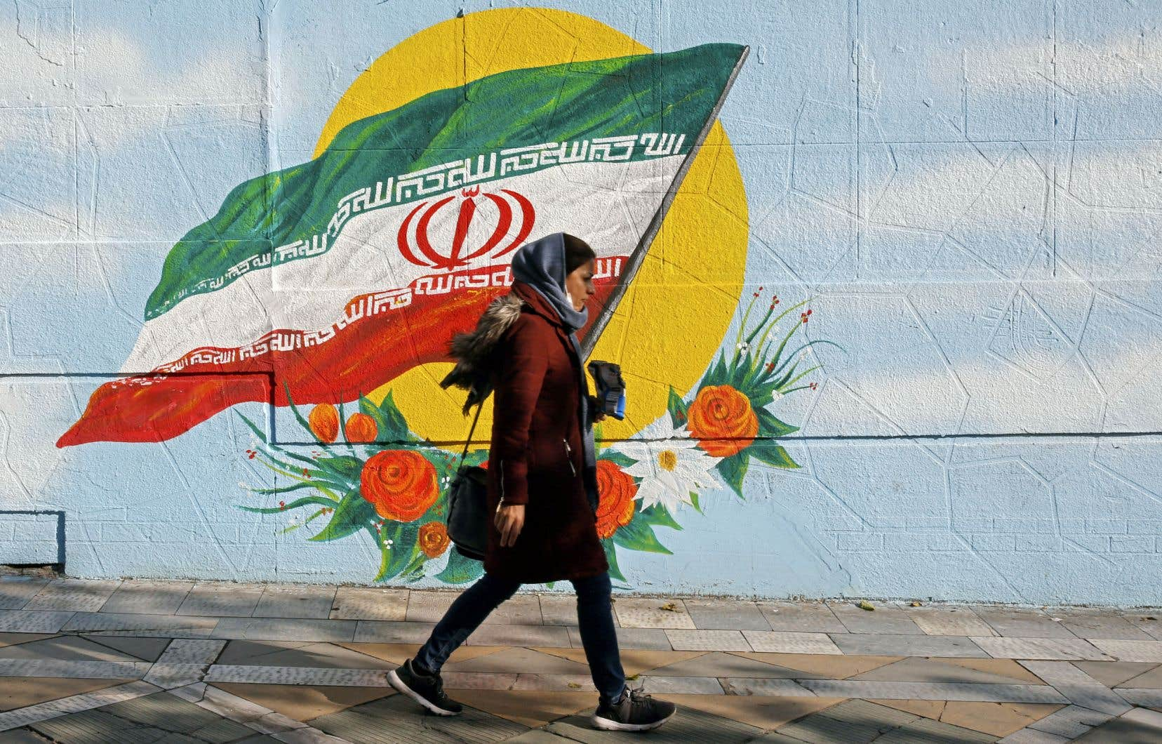 Une femme passe devant une murale représentant le drapeau de la République islamique. Des manifestants ont appelé au retour de la monarchie.