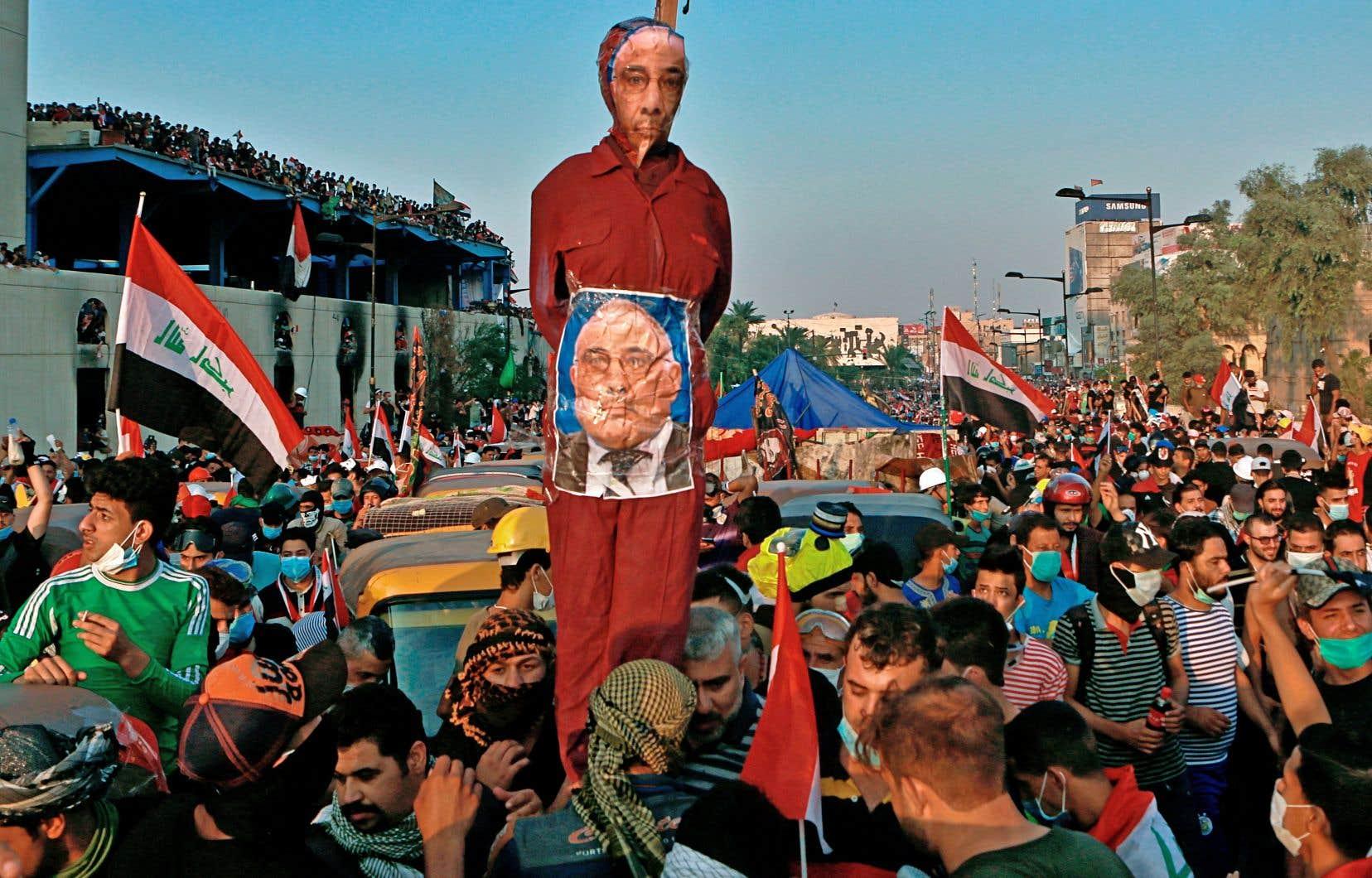 La démission du premier ministre entré en exercice en octobre 2018, ici en pantin lors d'une manifestation, marque un nouveau développement dans un Irak à feu et à sang.