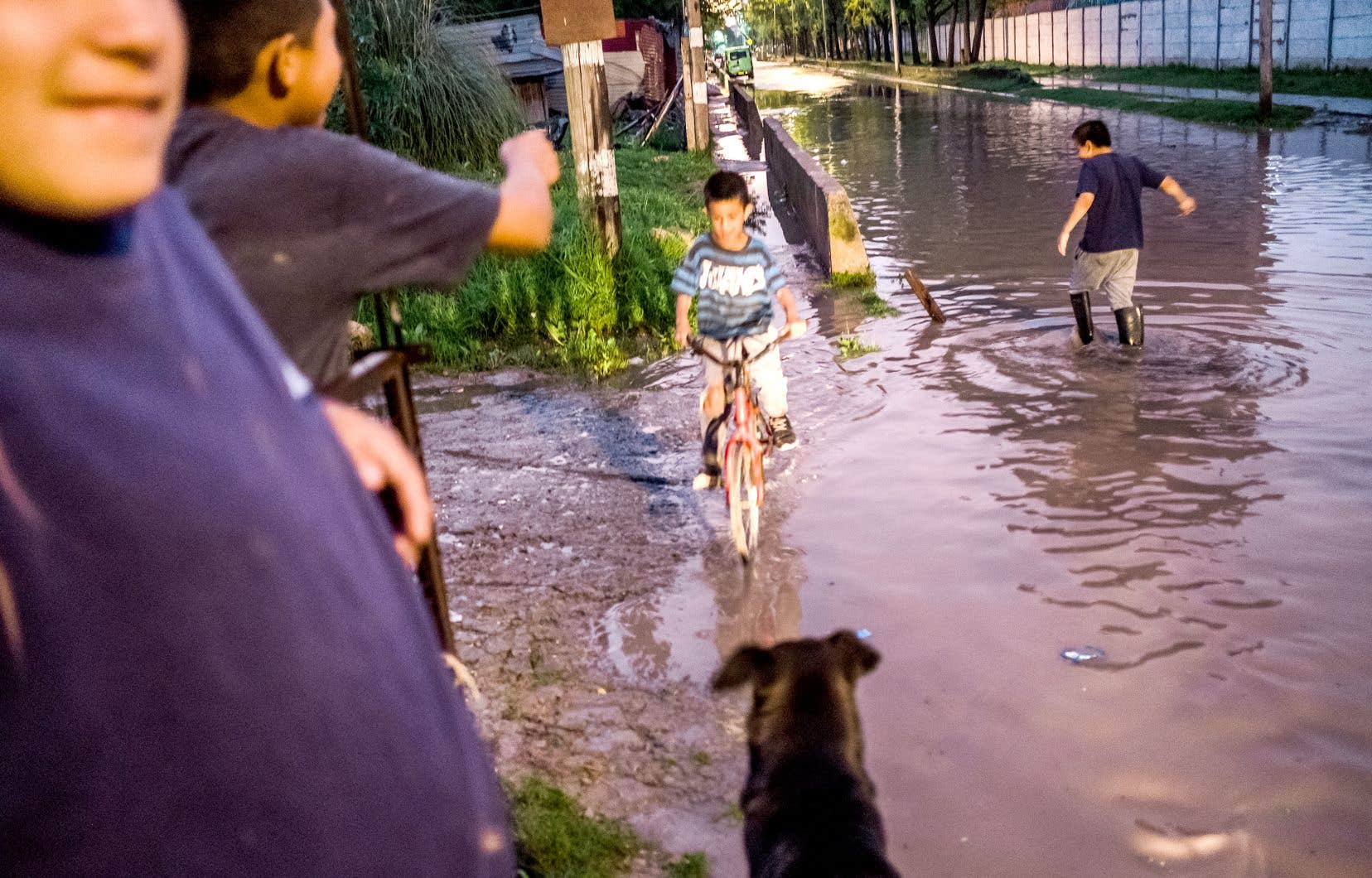 Des enfants jouent dans une rue emplie d'eau de Villa Inflamable.
