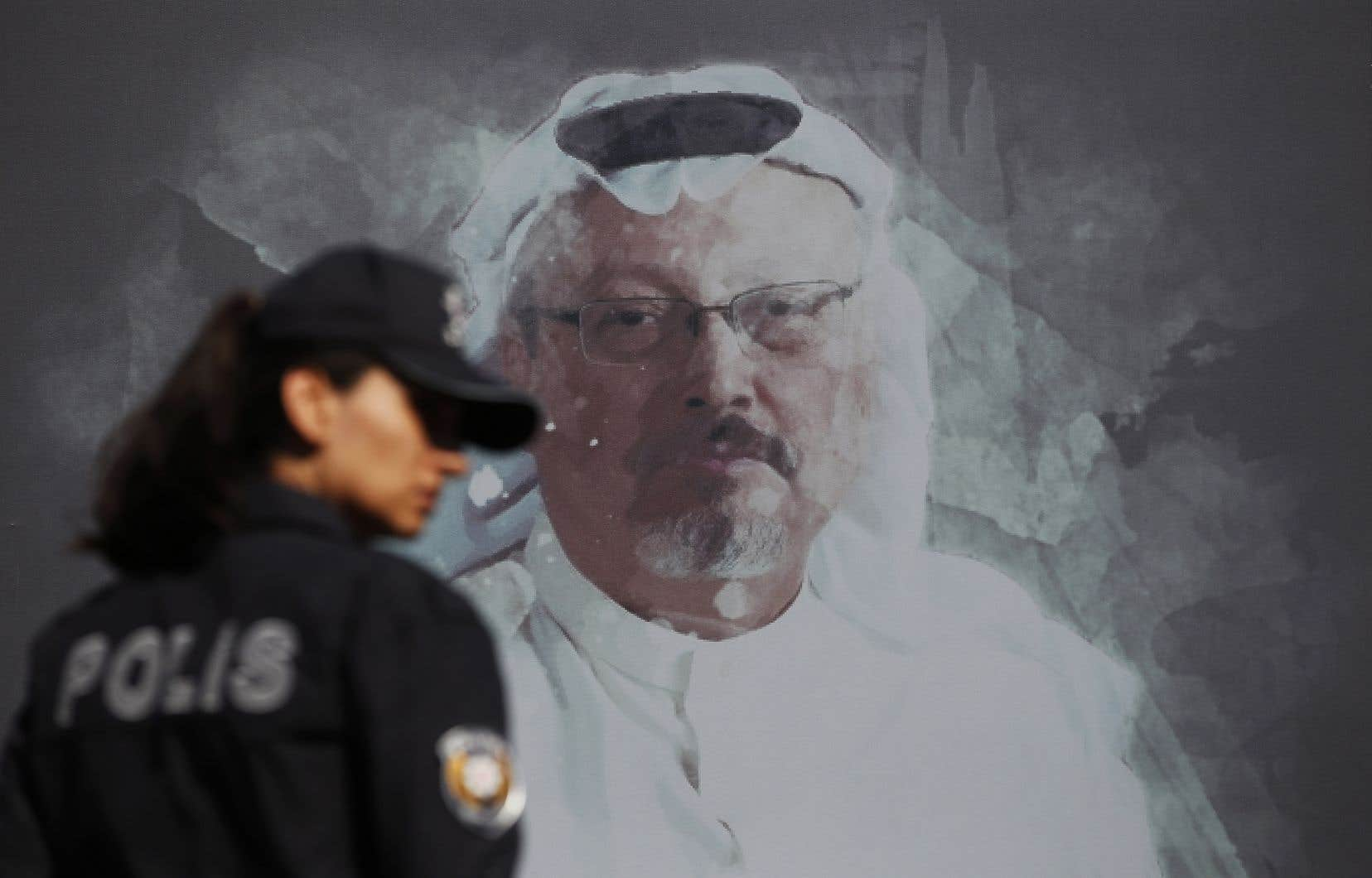 Une policière turquepasse devant une image représentant le journaliste saoudien assassiné Jamal Khashoggiprès du consulat d'Arabie saoudite à Istanbul, avant une cérémoniemarquant le premier anniversaire de sa mort, le 2 octobre 2019.