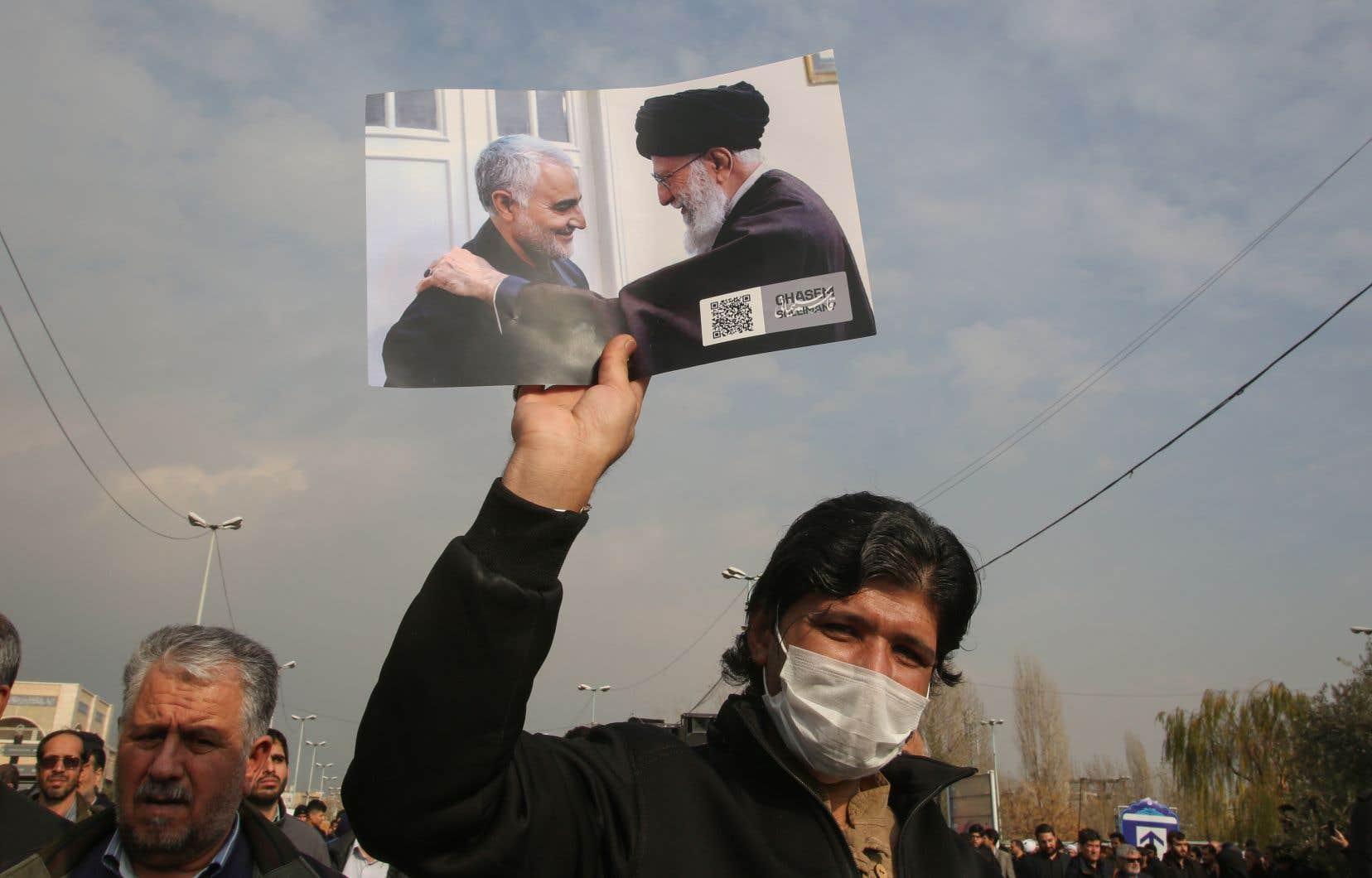 Un manifestan iranien brandit une image où figure le général Qassem Soleimani, tué vendredi dans un raid américain à Bagdad, en compagnie de l'ayatollah Khamenei.