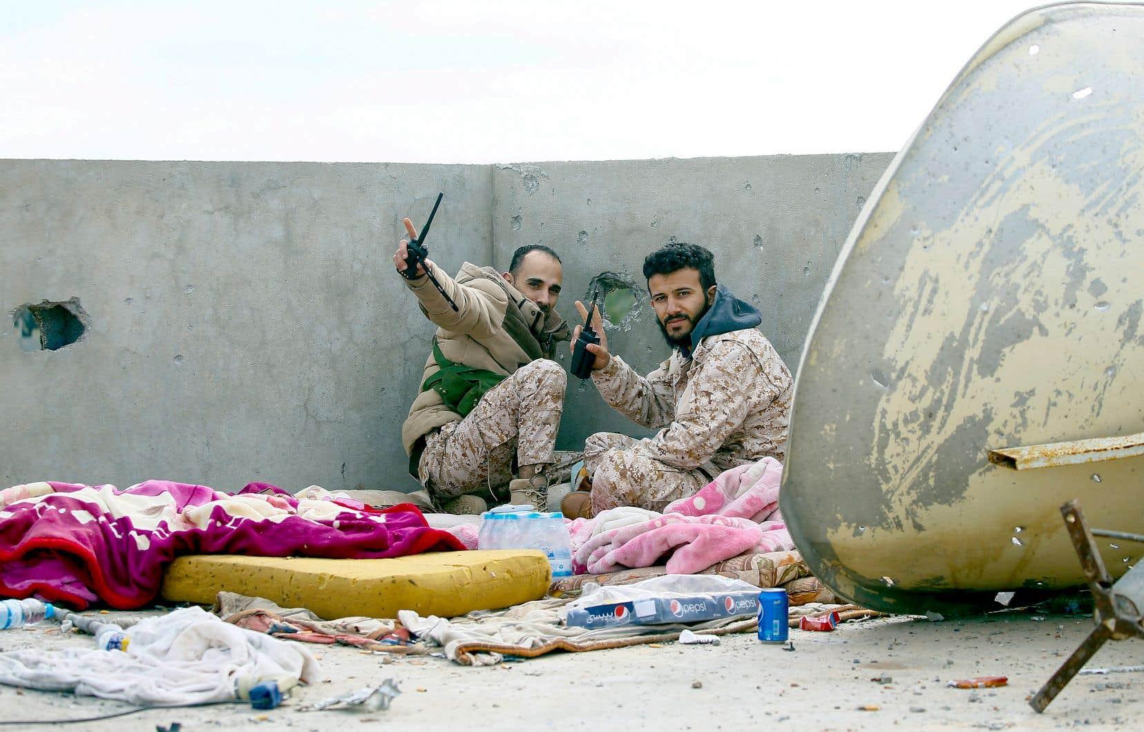 Deux soldats du gouvernement d'union nationale faisaient une pause dimanche près de Tripoli.