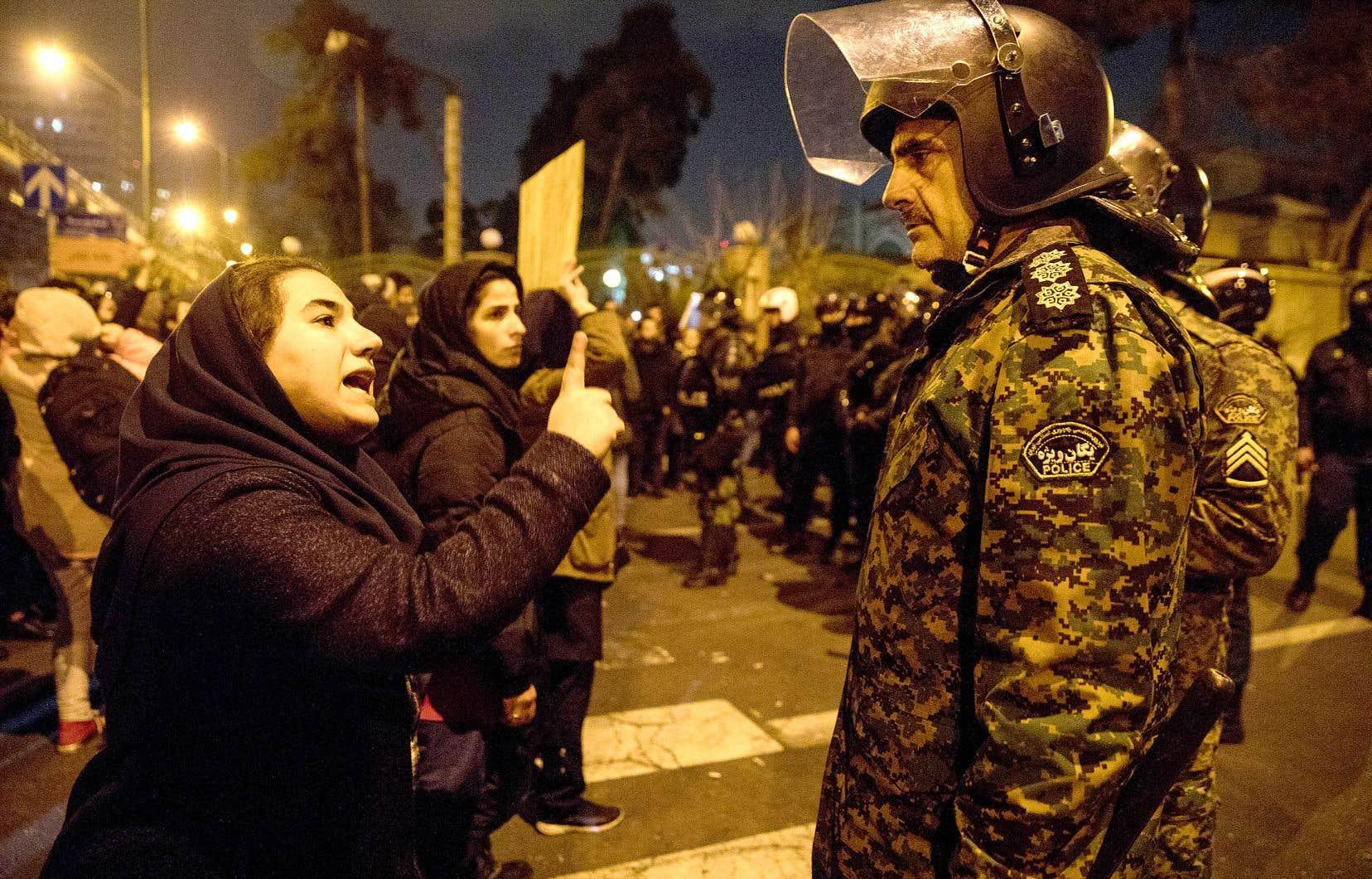 Une femme invectivant un policier antiémeute lors d'un rassemblement en l'honneur des victimes du vol d'Ukraine Airlines, à Téhéran, dimanche