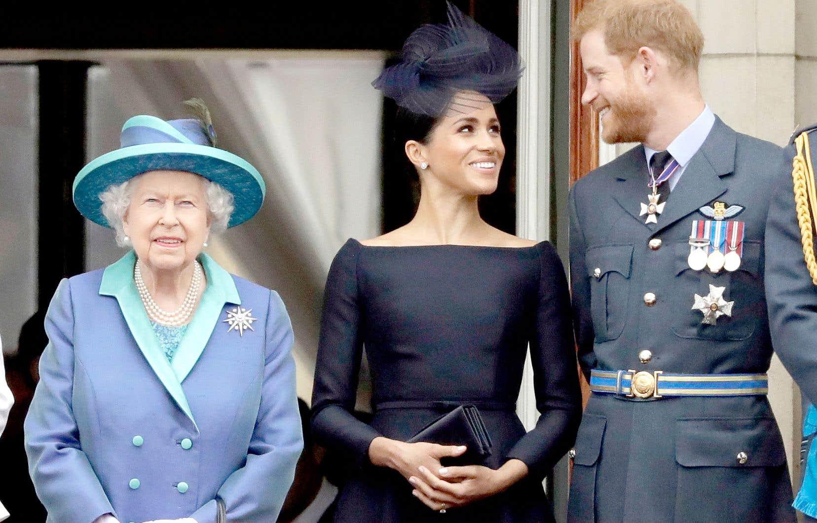 La reine Élisabeth II, la duchesse de Sussex, Meghan Markle, et le Prince Harry lors d'une cérémonie à Buckingham Palace en 2018