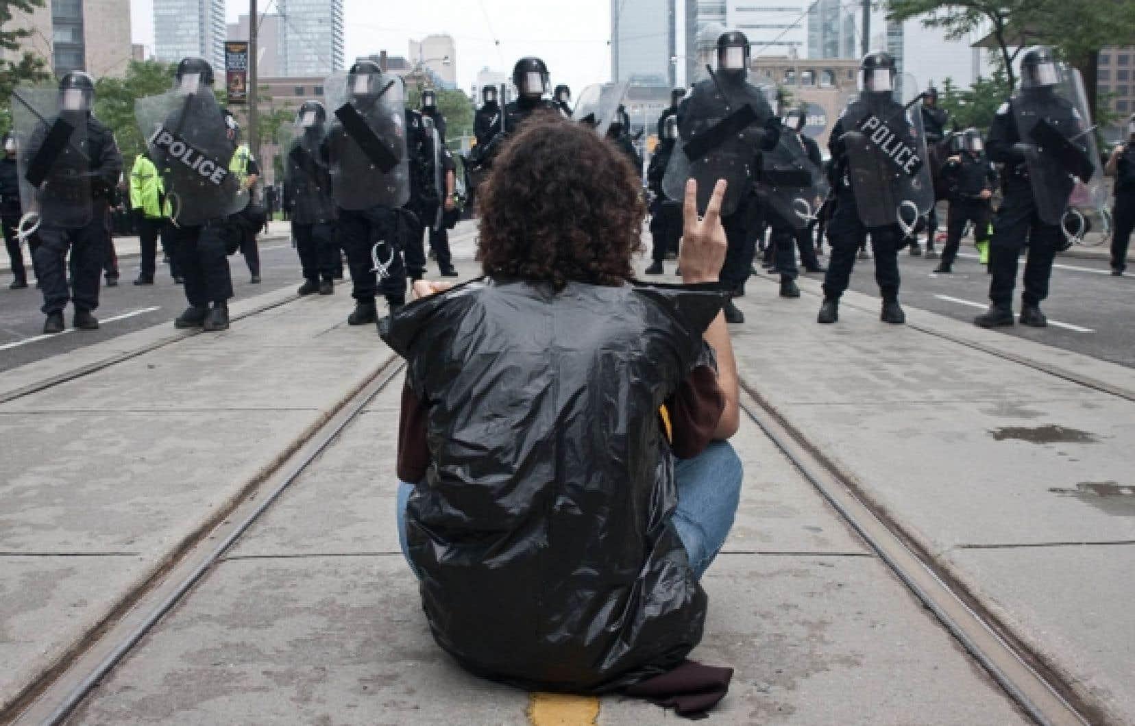 Un manifestant opposé au G20 fait face à un cordon policier à Queen's Park, le samedi 26 juin 2010.<br />