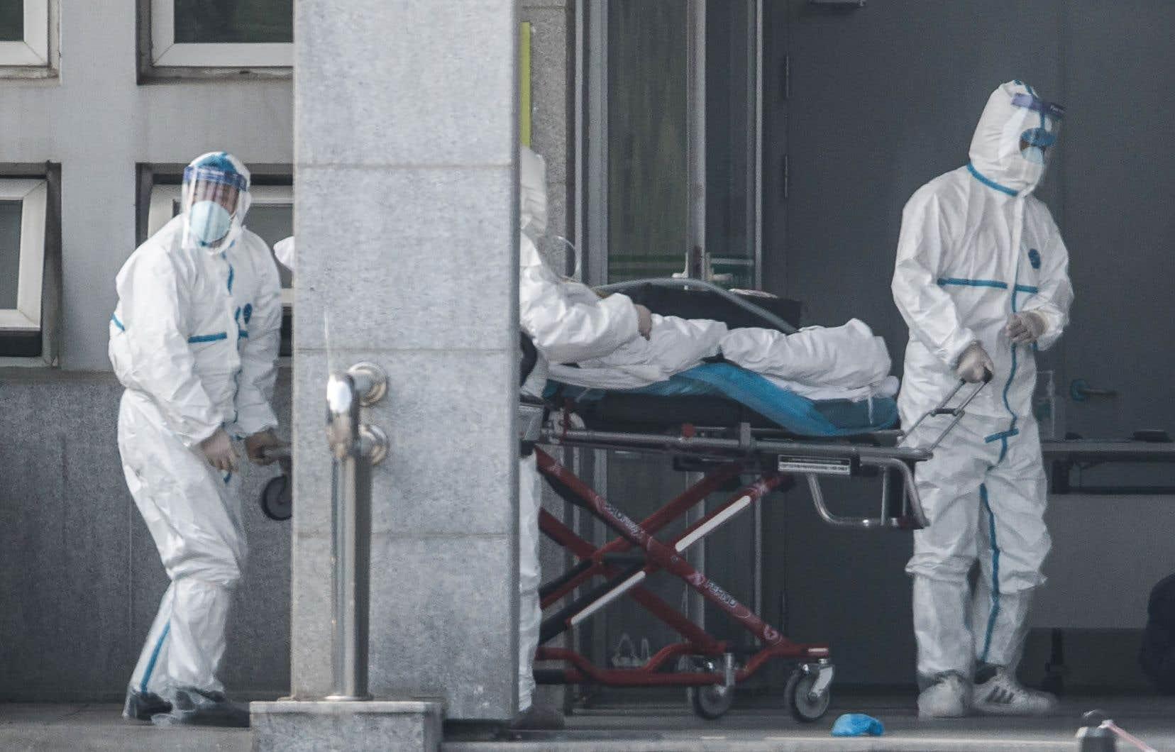 Des membres du personnel médical transportent un patient à l'hôpital de Jinyintan, où des patients infectés par un mystérieux virus semblable au SRAS sont traités, à Wuhan, dans la province centrale du Hubei en Chine, le 18 janvier 2020.