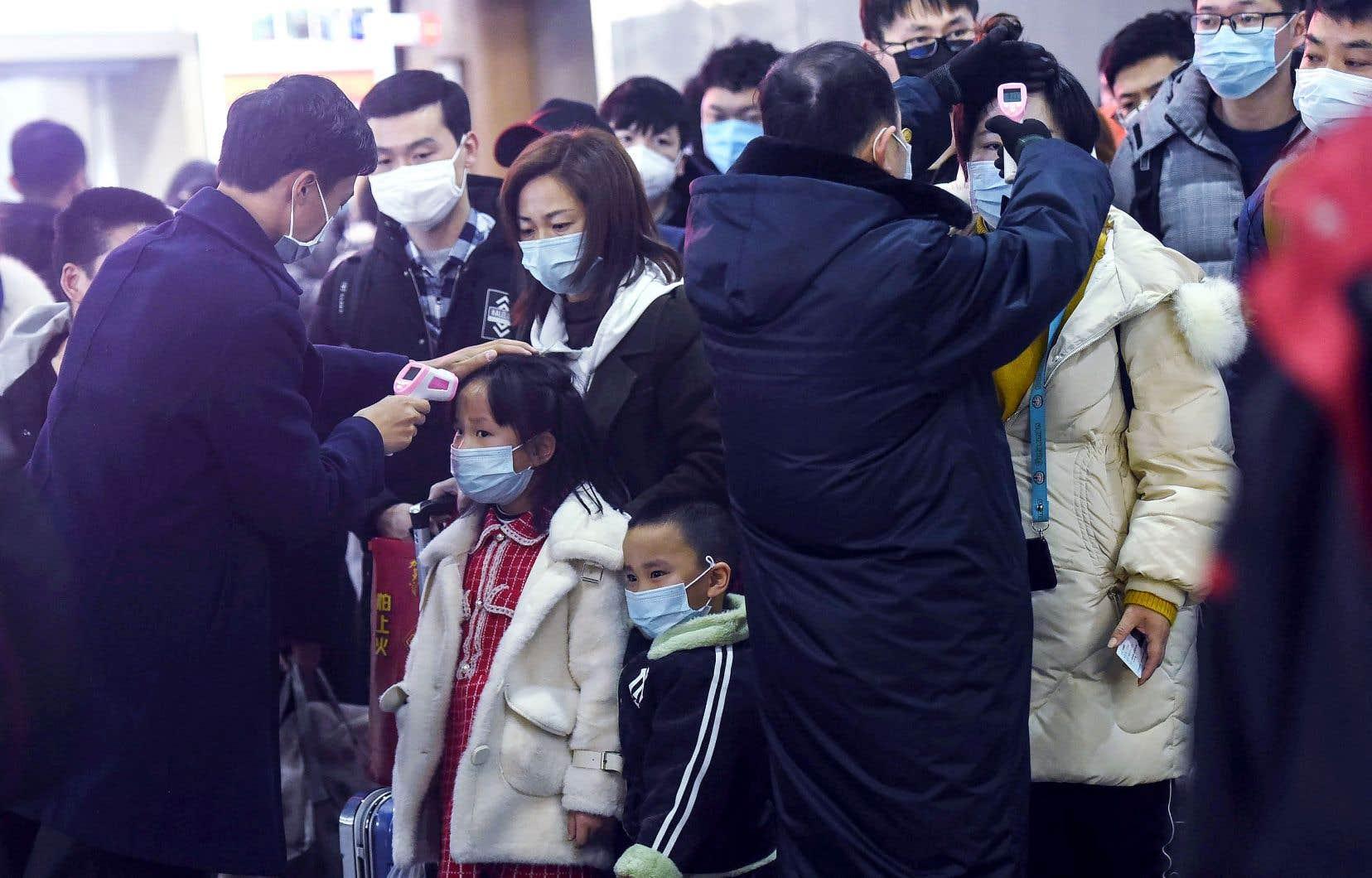 Des employés d'une station de train chinoise de Hangzhou vérifient la température corporelle de voyageurs en provenance de Wuhan, épicentre de l'épidémie.