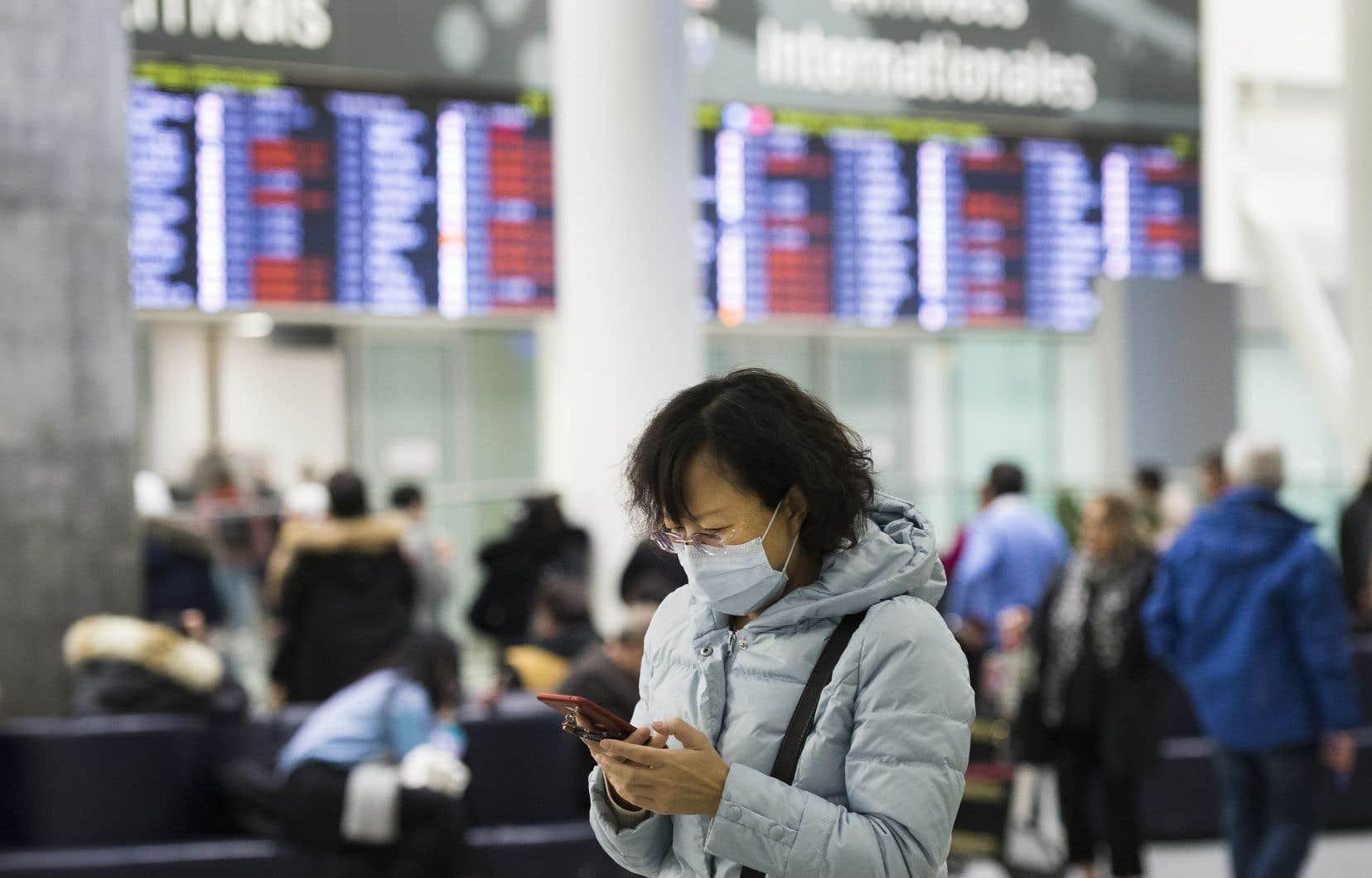 Un grand nombre de voyageurs portaient des masques à l'aéroport Pearson de Toronto, dimanche, pour se protéger du coronavirus chinois.