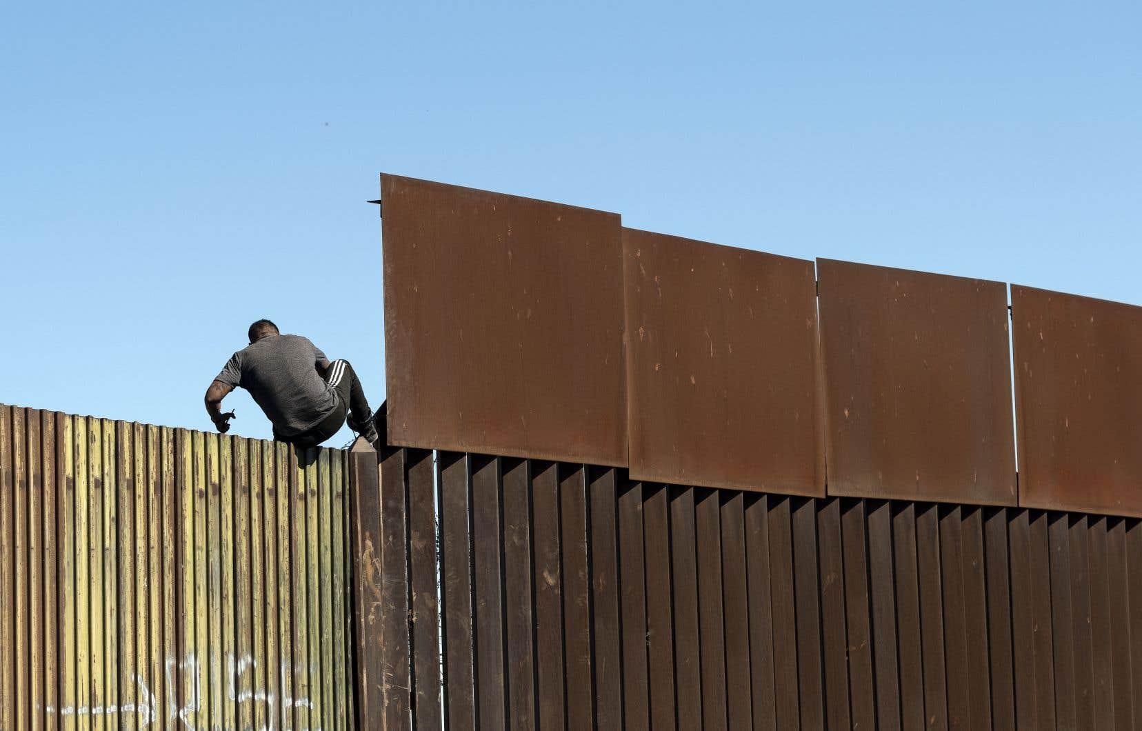 Un homme traverse la barrière frontalière américano-mexicaine de Mexicali à Calexico, dans l'État de Baja California, au Mexique, le 11 février 2020.