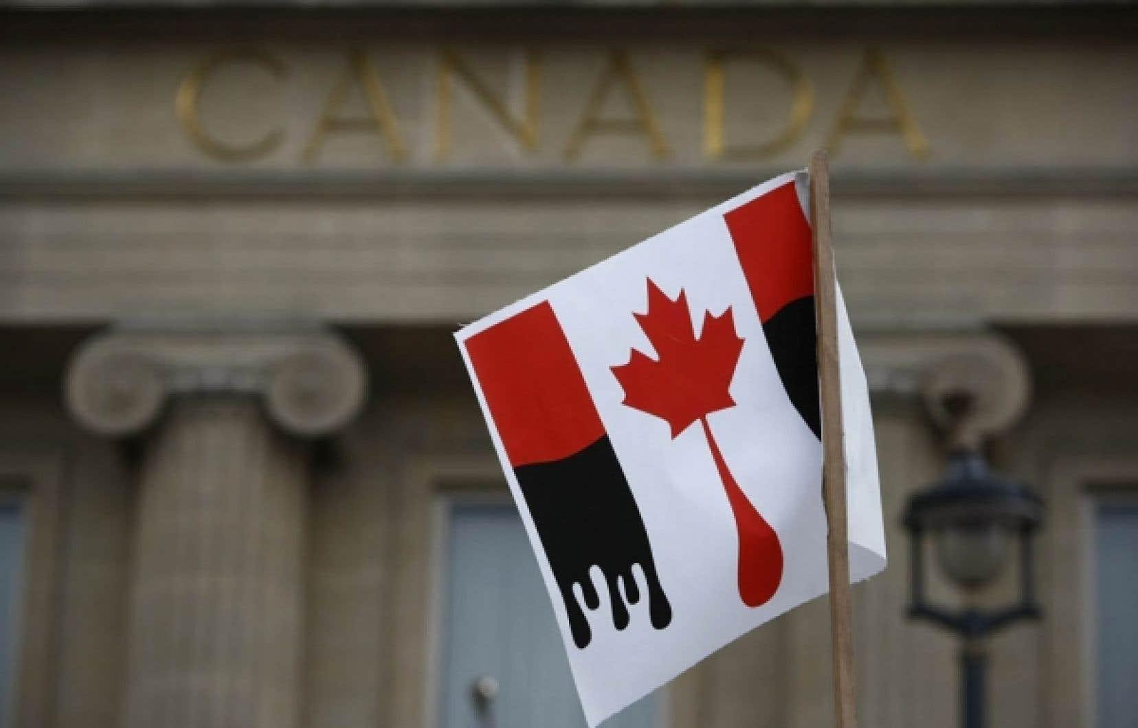 Manifestation contre les sables bitumineux devant l'ambassade canadienne à Londres en février dernier. Le Canada est maintenant accusé de s'en prendre aux politiques vertes des autres pays.<br />