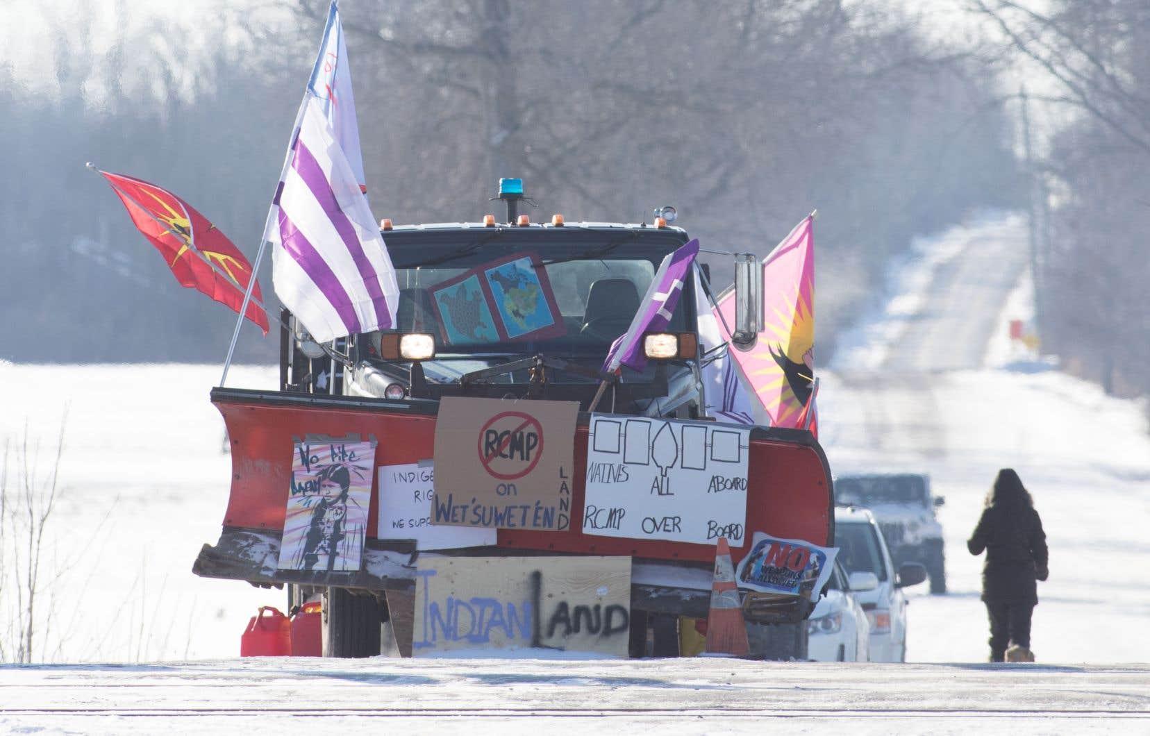 Un camion avec des drapeaux et des affiches se tient près de la voie ferrée bloquée, au neuvième jour du blocus ferroviaire, à Tyendinaga, près de Belleville, en Ontario.