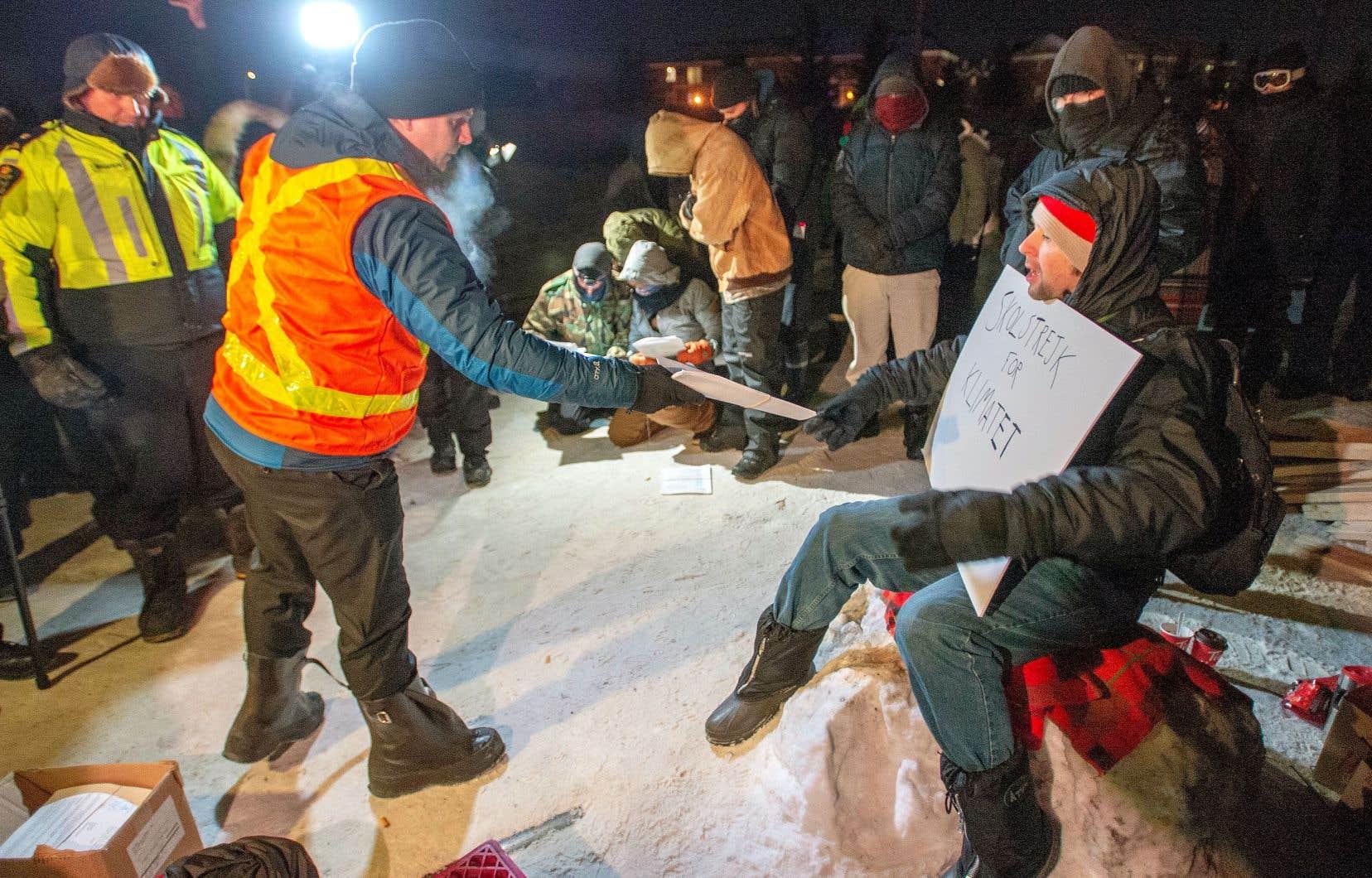 Les policiers ont remis aux manifestants l'injonction accordée par la cour au CN qui leur intime de lever le camp entravant la voie ferrée.