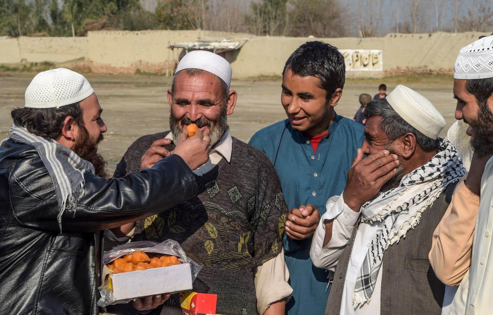 Dans le camp de réfugiés deKhurasan, en banlieue de Peshawar,un homme distribue des pâtisseries pour célébrer la «réduction des violences».